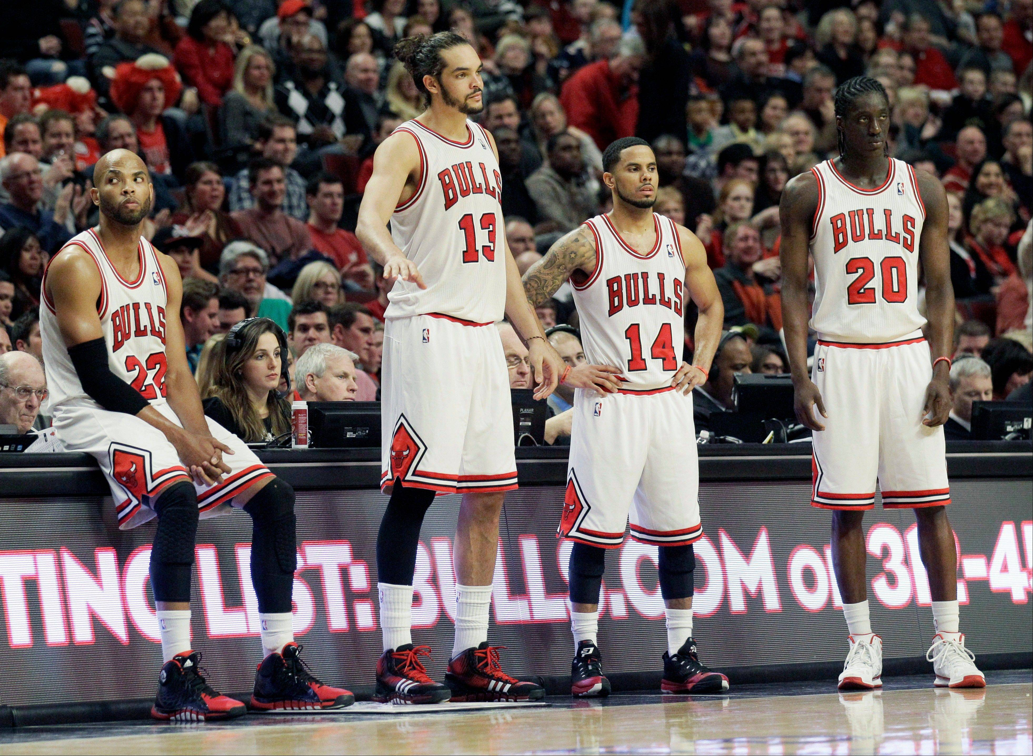 The Bulls' Taj Gibson, from left, Joakim Noah, D.J. Augustin and Tony Snell react to just how bad things were going in Saturday night's loss to the Dallas Mavericks.