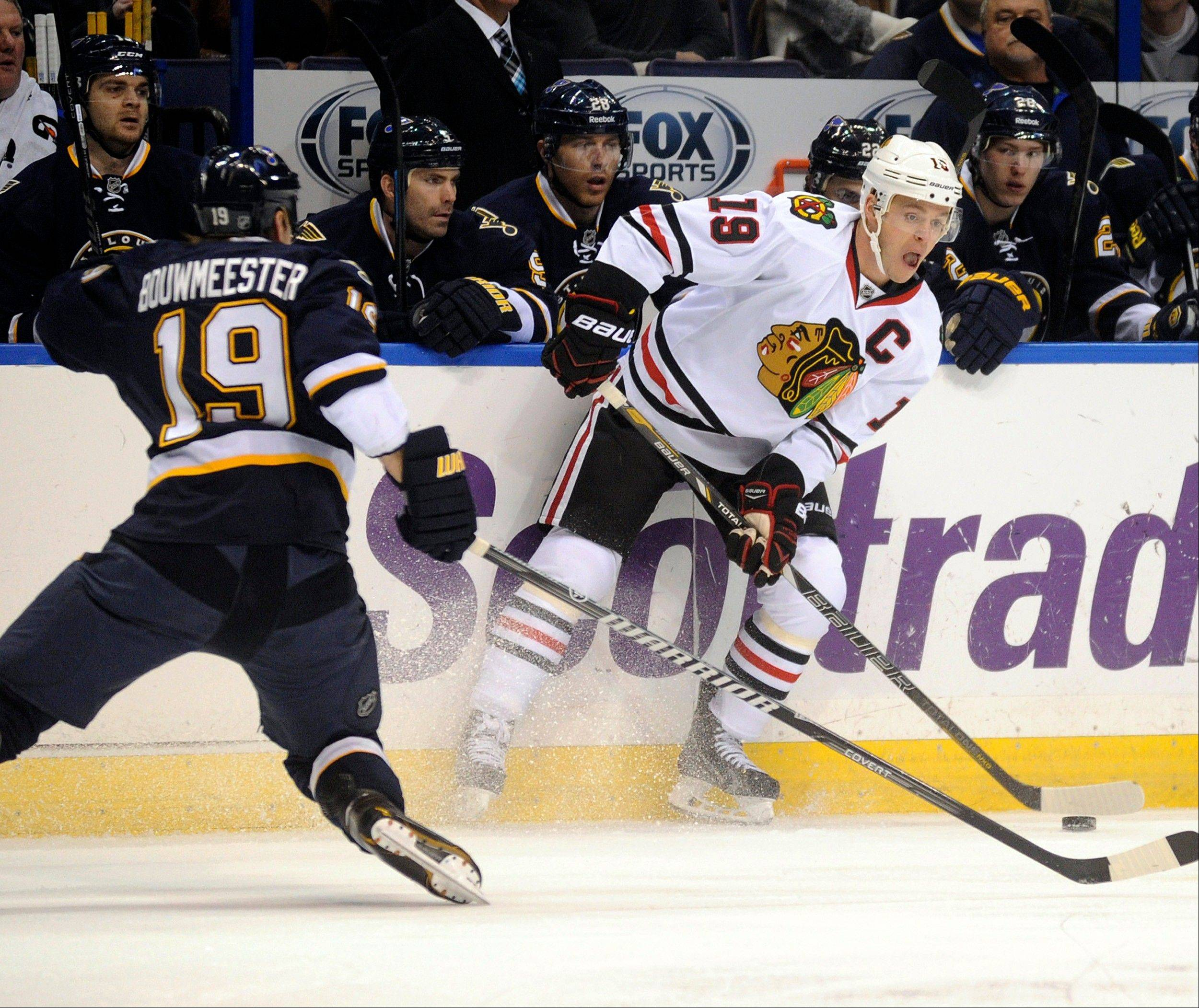 The Chicago Blackhawks' Jonathan Toews, right, looks to pass around the St. Louis Blues' Jay Bouwmeester during the first period Saturday in St. Louis.