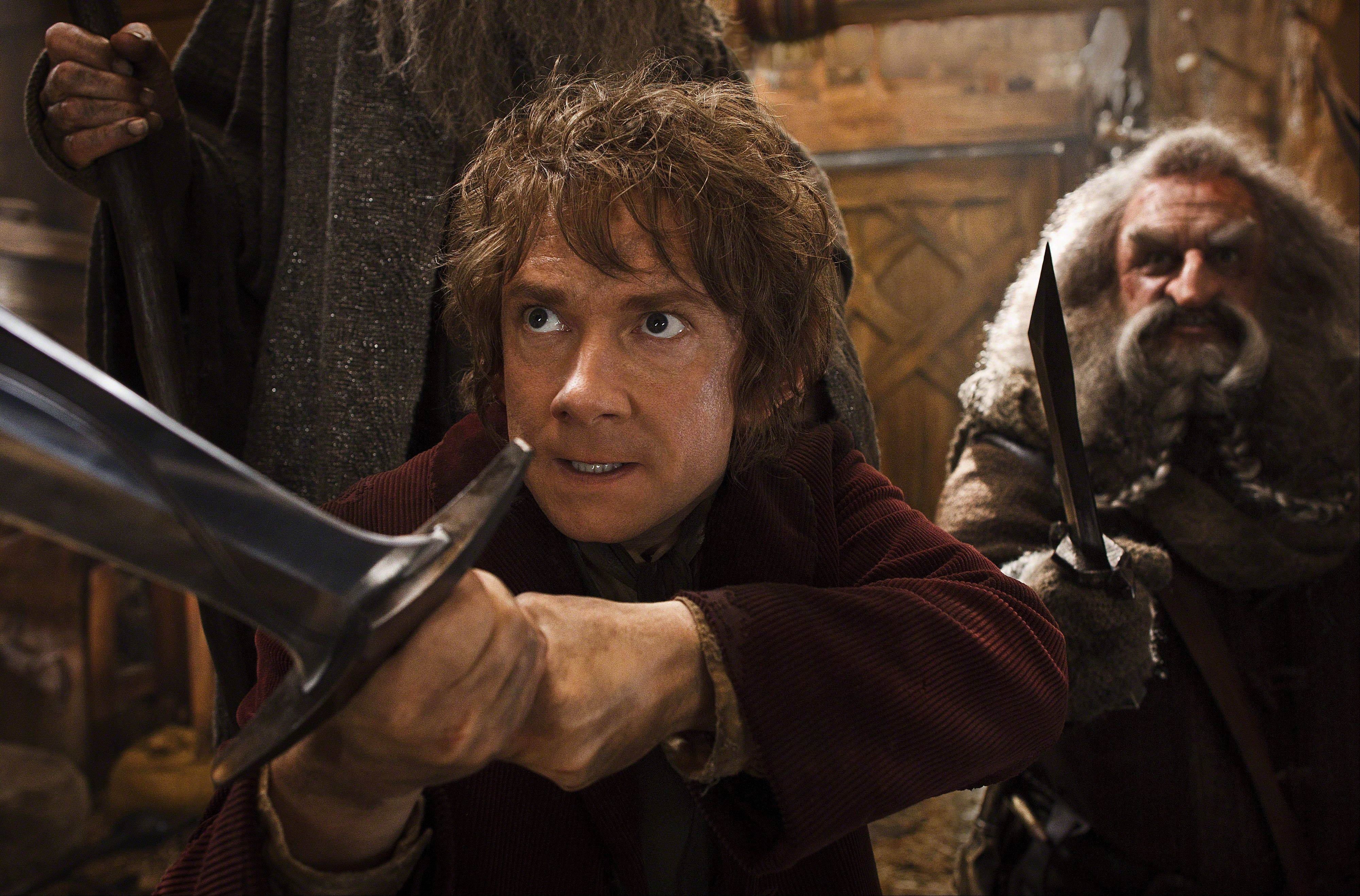 This image released by Warner Bros. Pictures shows Martin Freeman, left, and John Callen in a scene from �The Hobbit: The Desolation of Smaug.�The Hobbit: The Desolation of Smaug� continued to top the box office, landing at No. 1 over the Christmas holiday for the third weekend in a row.