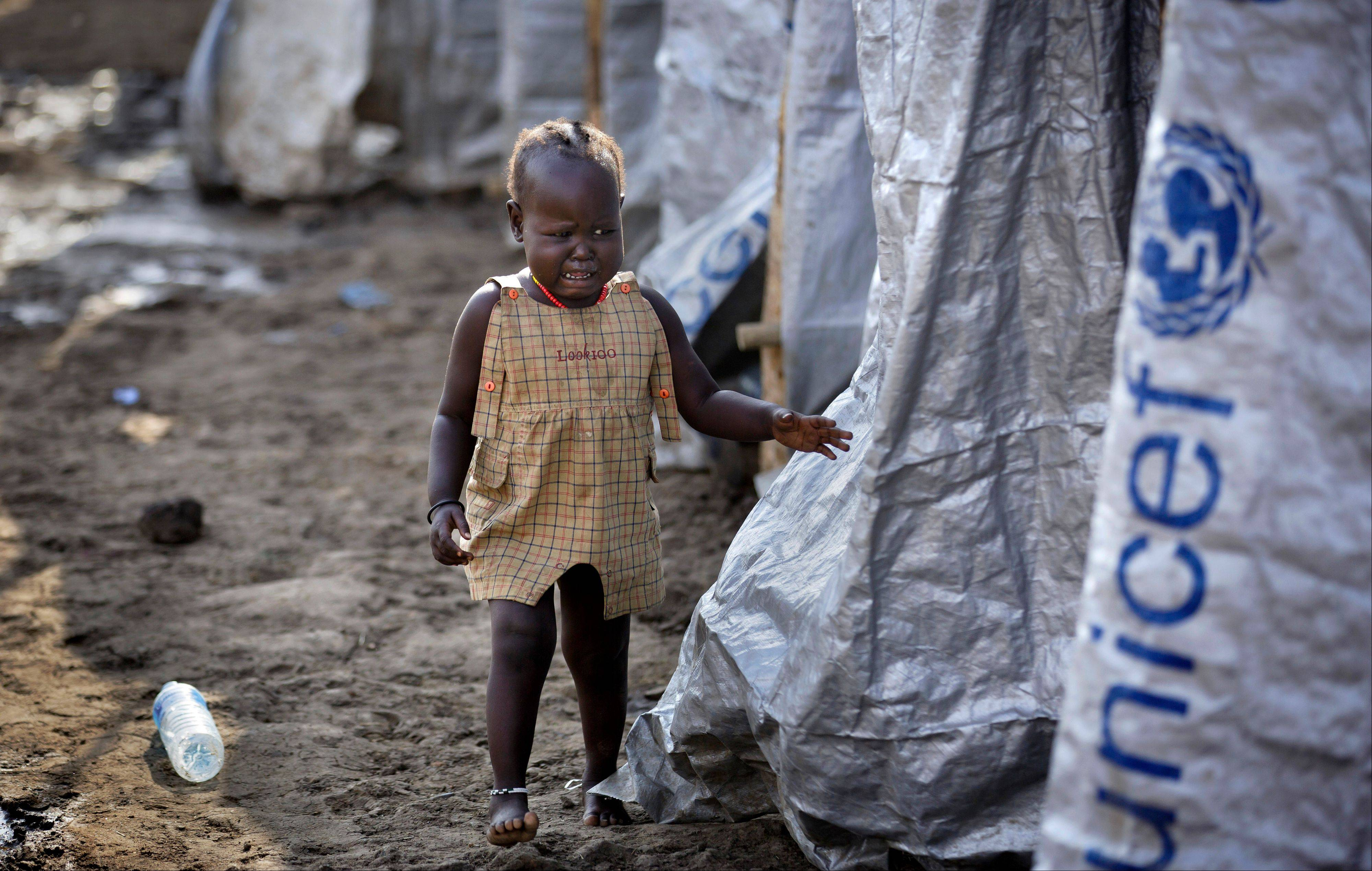 A young displaced girl starts crying after the relative she was with disappears into a row of latrines, at a United Nations compound which has become home to thousands of people displaced by the recent fighting, in the capital Juba, South Sudan, Sunday.