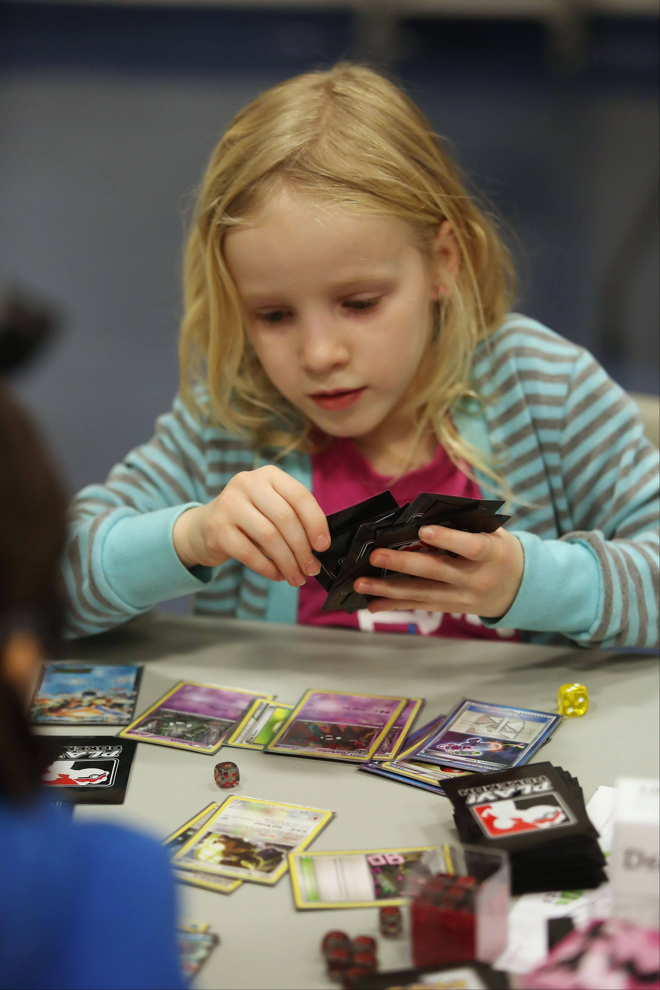 Grace Ours, 7, of Naperville plays her cards during the Pokemon Trading Card Game City Championships at the Sciences and Arts Academy in Des Plaines on Sunday. The tournament attracted 89 participants from all over the Midwest, including St. Louis and Madison, Wis. Players from three age divisions competed to earn points toward a potential invitation to the 2014 Pokemon World Championships in Washington, D.C., next summer.