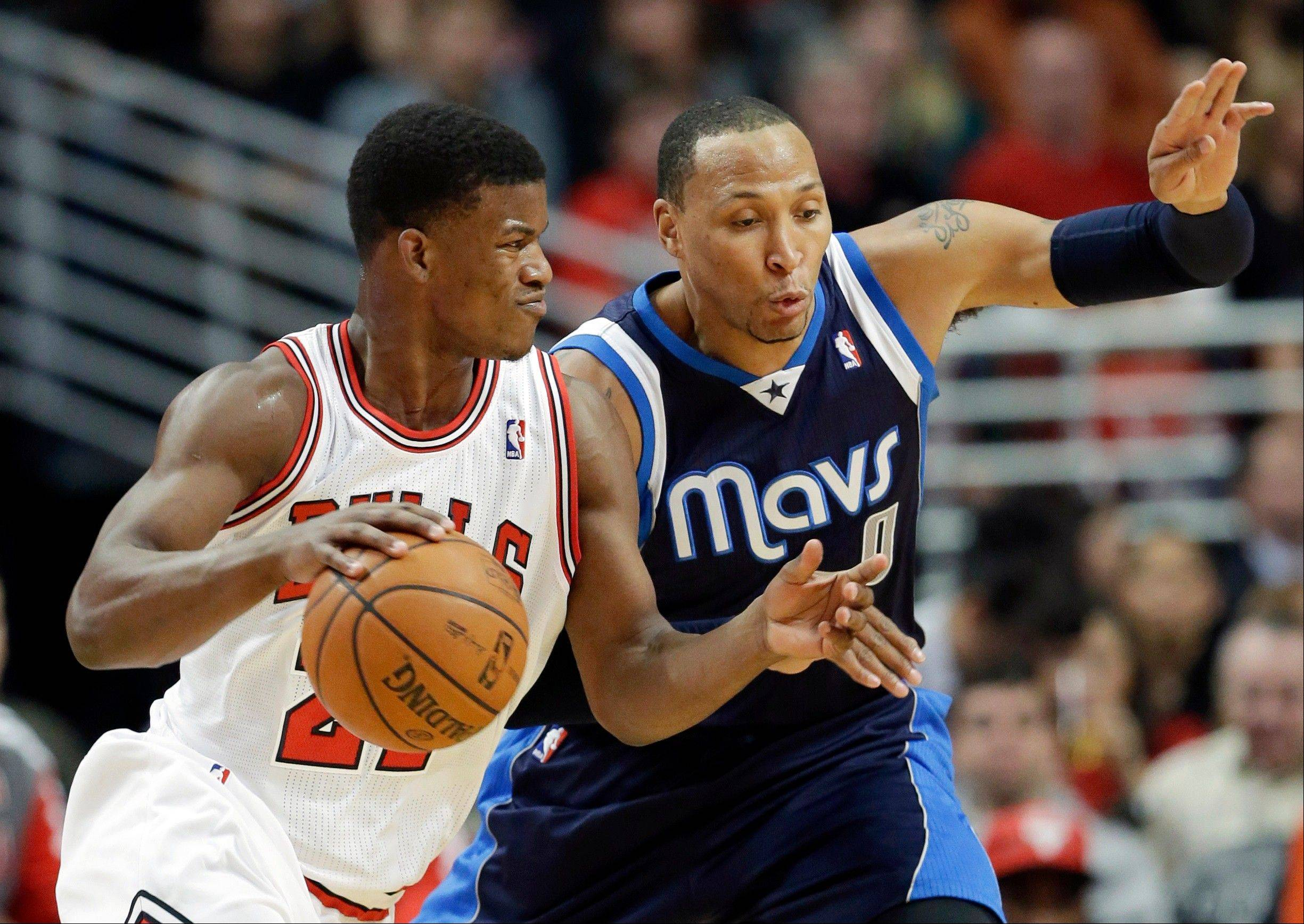 Bulls guard Jimmy Butler drives against Mavericks forward Shawn Marion on Saturday. Butler aggravated a turf toe injury in the loss but says he�ll be ready to play Monday in Memphis.