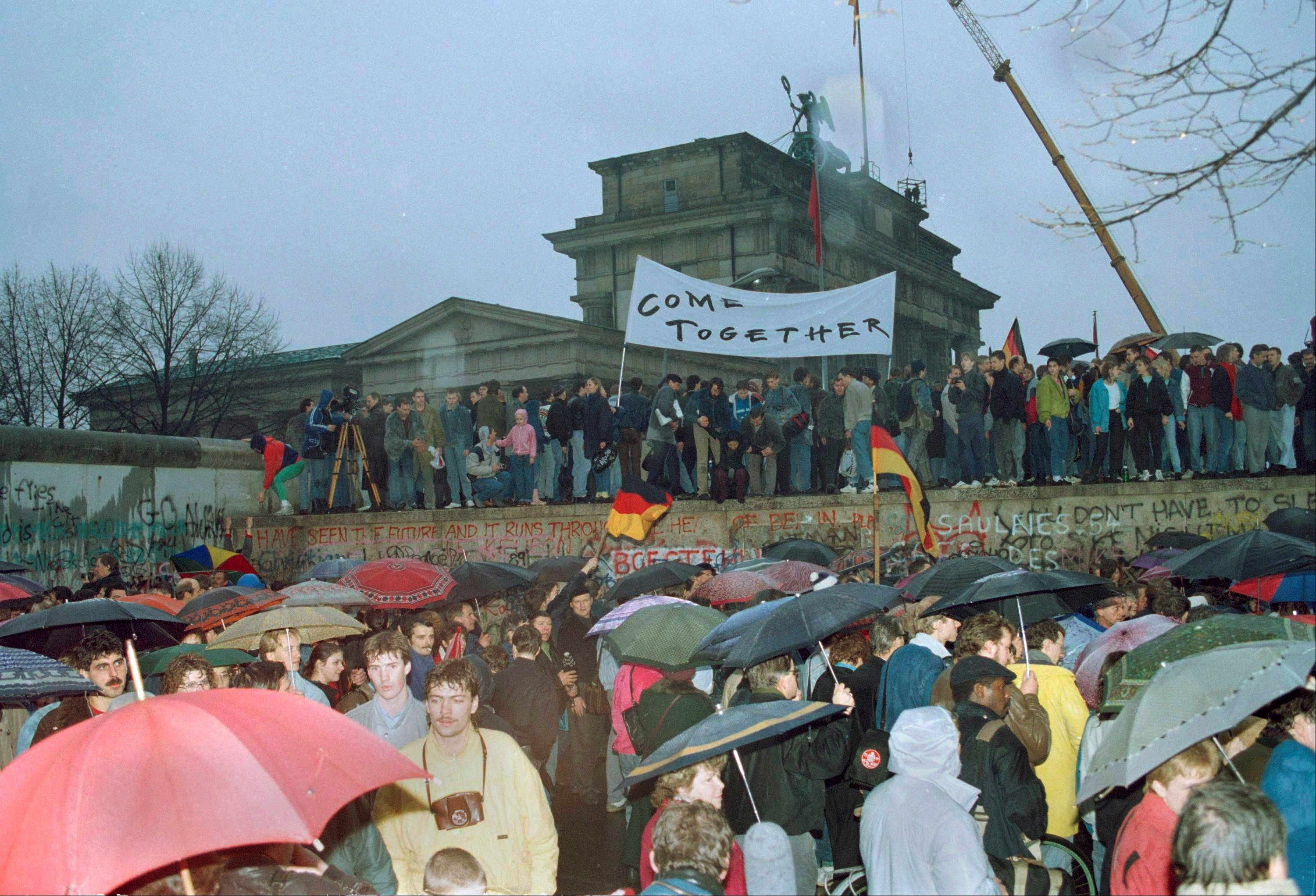This Dec. 22, 1989 file photo shows thousands of Berliners crowding at the Brandenburg Gate and stand on top of the Berlin Wall after two new crossings were made, reuniting the divided city after 28 years. In 2014, Berlin will mark 25 years since the wall was breached. Events and exhibits commemorating the anniversary will include an installation of illuminated balloons on a 7.5-mile path where Berlin was once divided by the wall into East and West.
