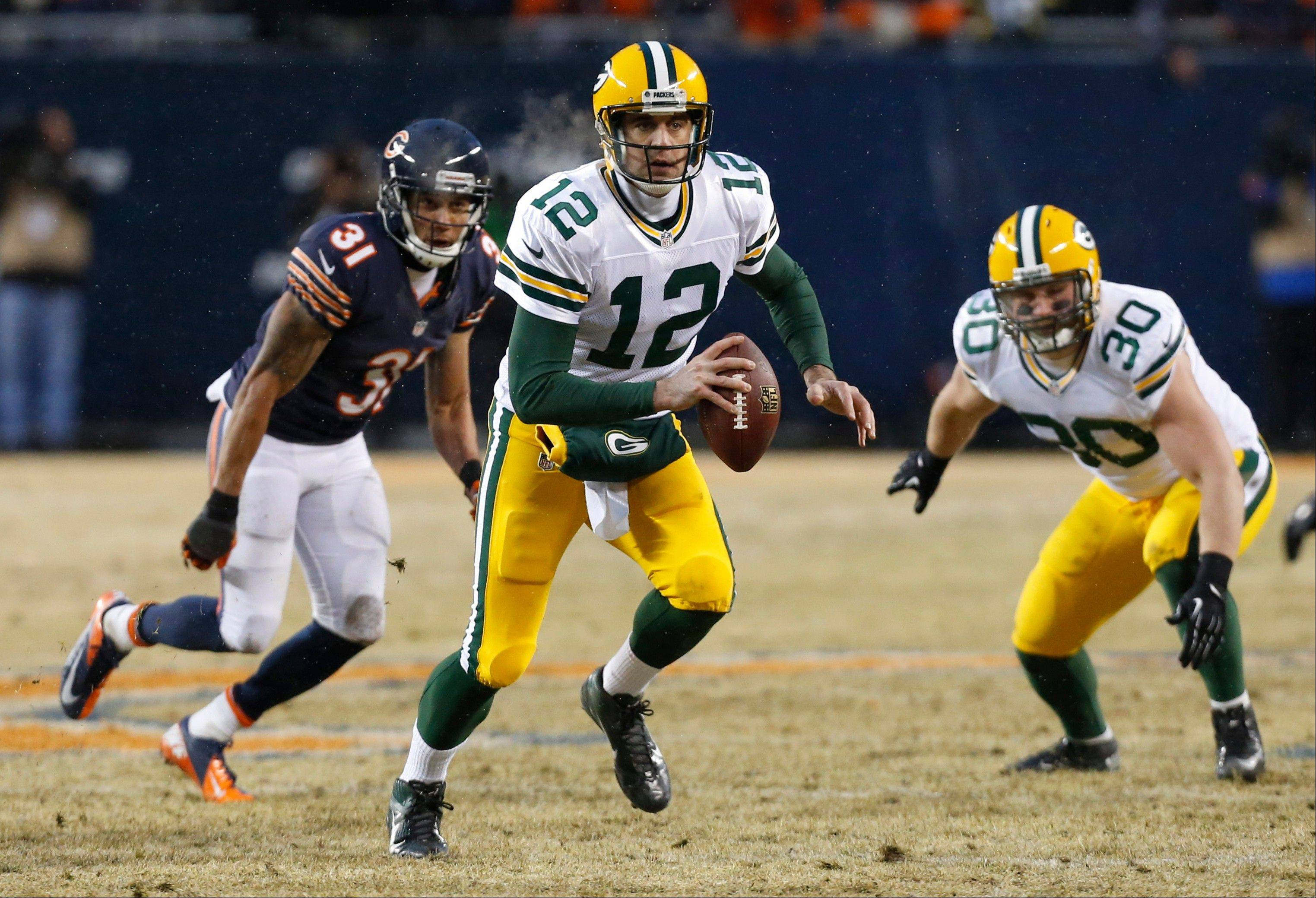 Green Bay Packers quarterback Aaron Rodgers (12) scrambles as he looks for a receiver during the first half.