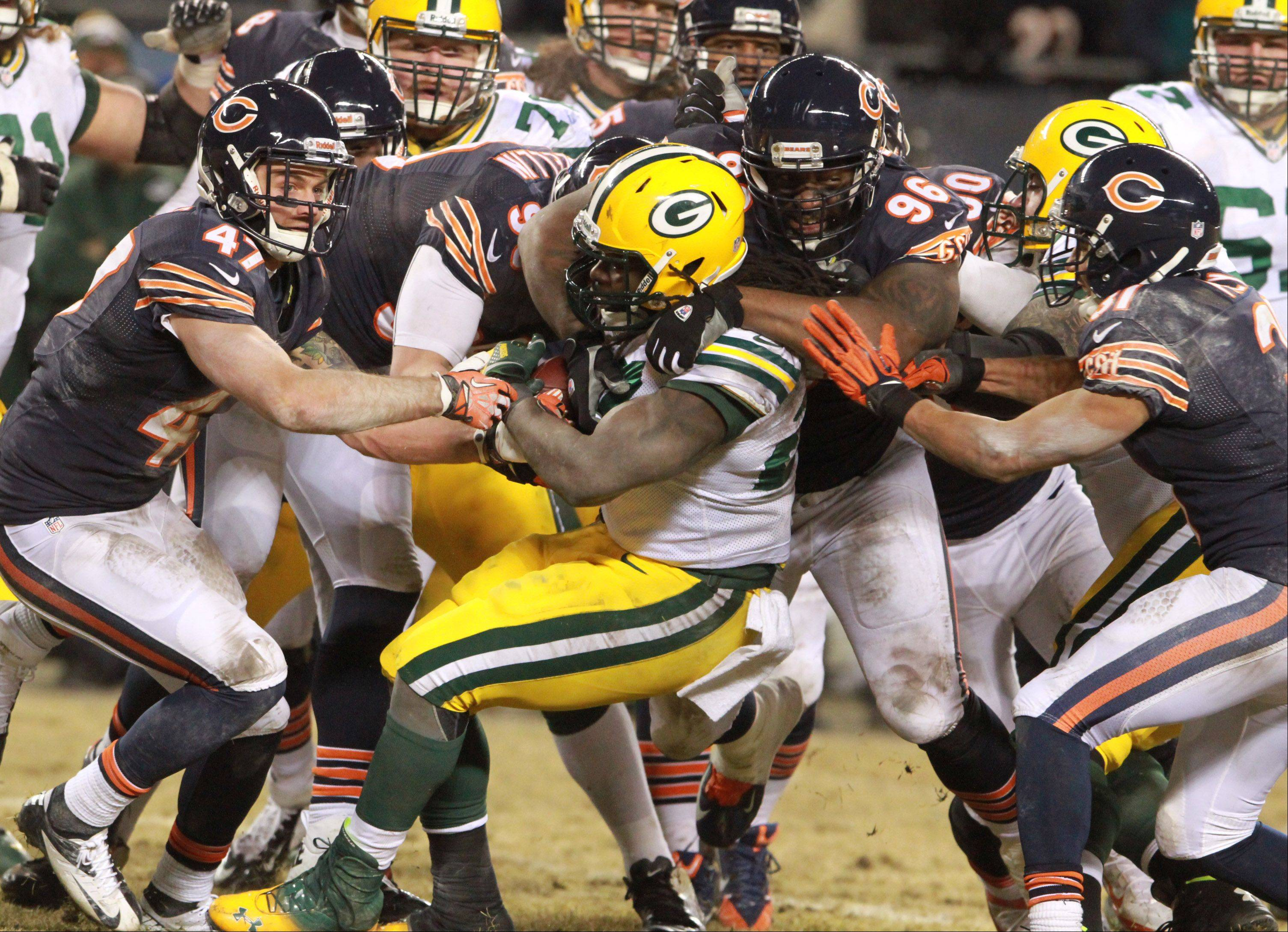 Green Bay Packers running back Eddie Lacy is dragged down by a host of Bears players including nose tackle Jeremiah Ratliff (96) on Sunday at Soldier Field in Chicago.