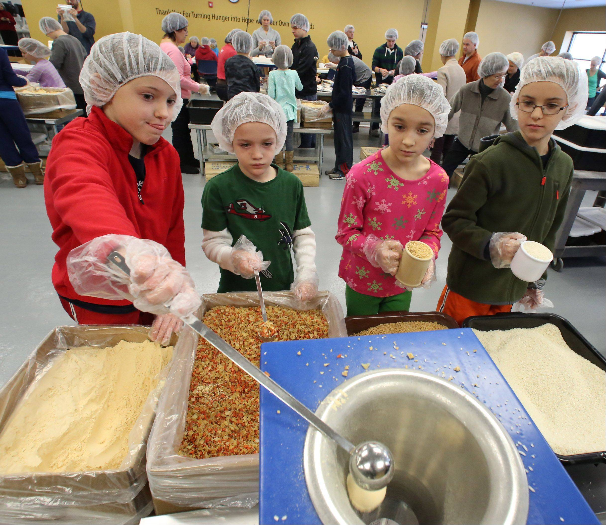 Megan Roberts, 8, left to right, pours an ingredient into a meal-packet, as Davis Hillback, 6, Abbie Hillback, 8, and Jonah Roberts, 8, all of Libertyville, wait their turn during a meal-packing event at Feed My Starving Children on Christmas Eve morning in Libertyville.