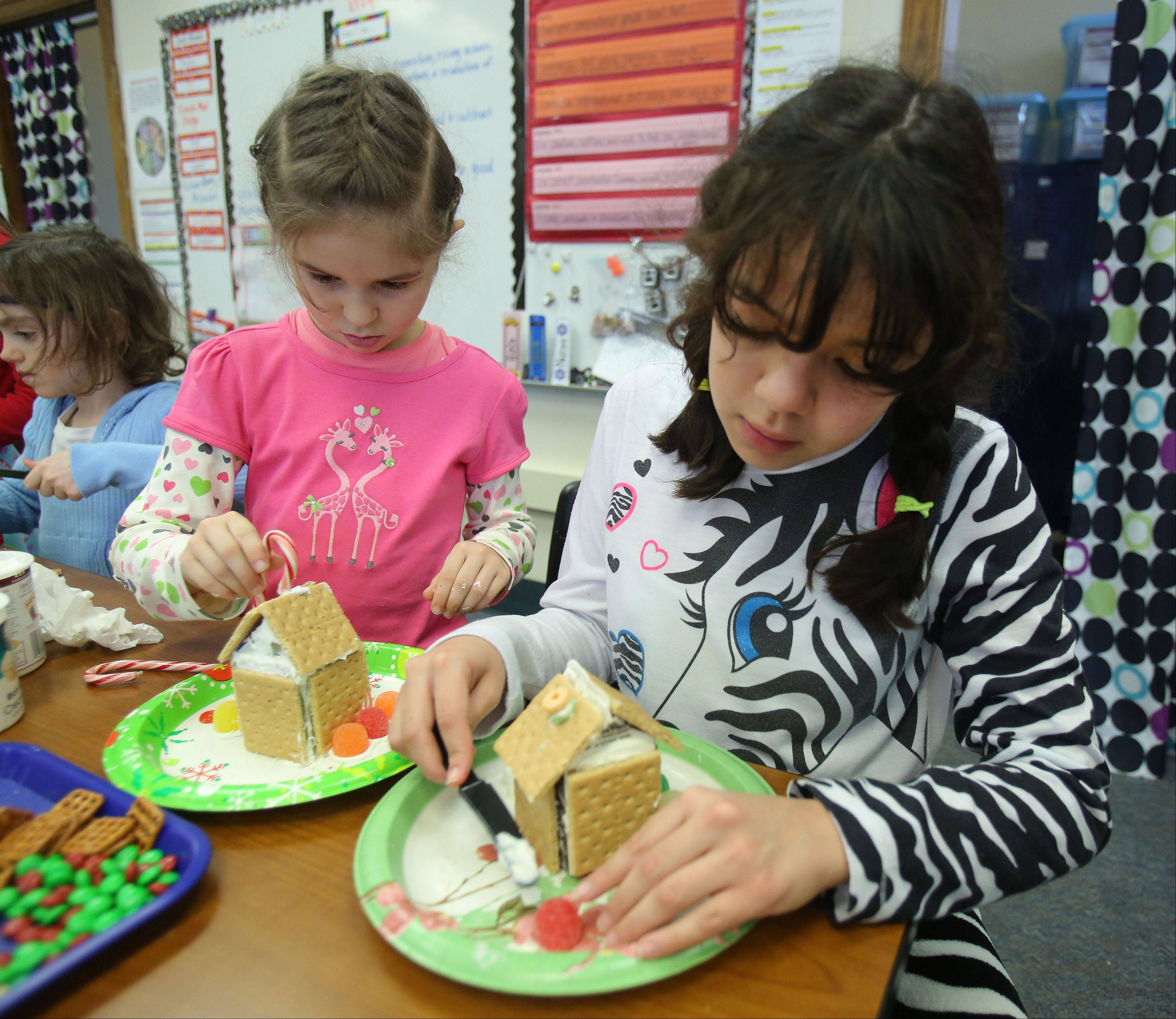 First grader Emily Psyhogios, left, and her fifth grade book buddy Payton Rodriguez, build gingerbread houses at Rockland Elementary School in Libertyville Thursday.