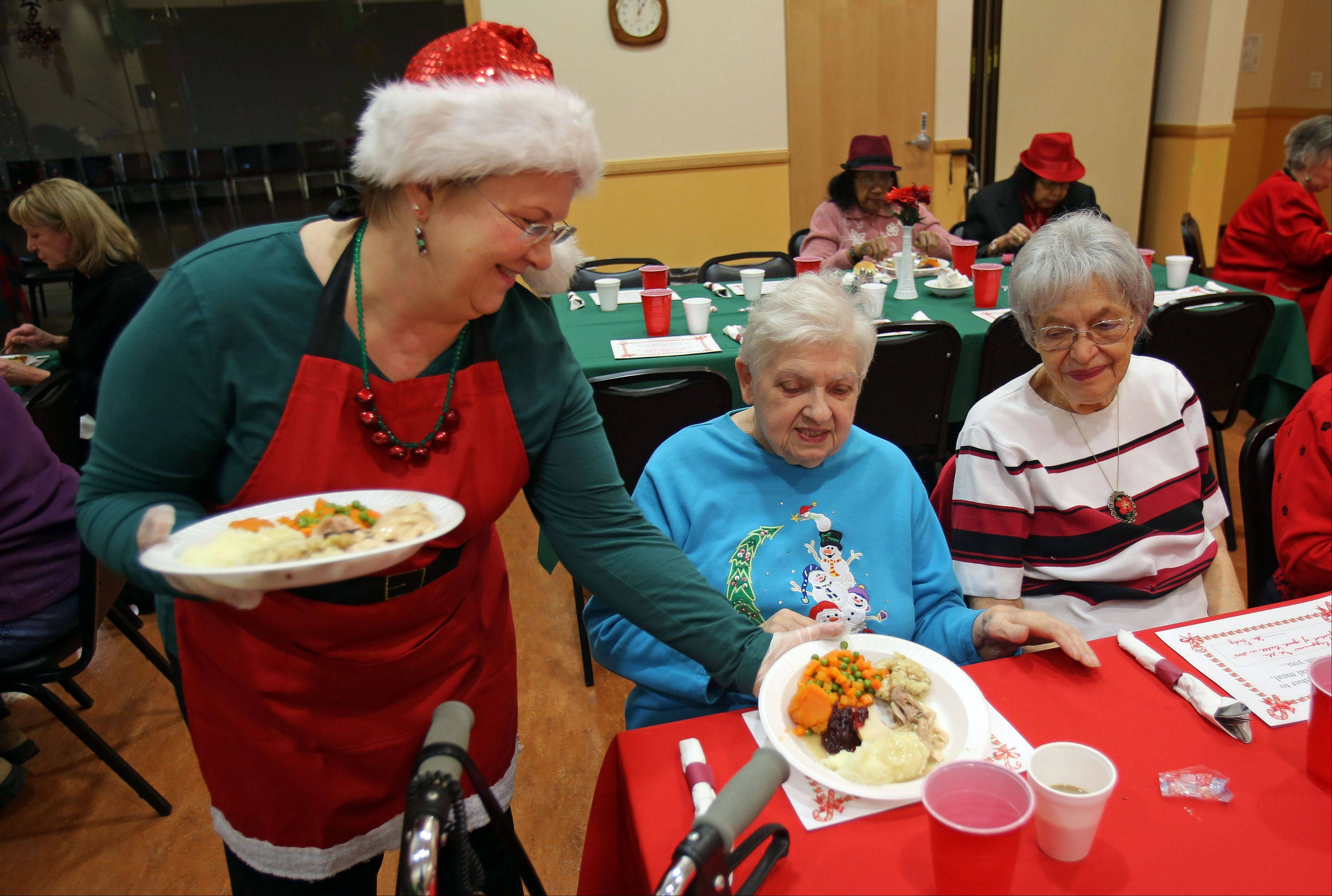 Des Plaines City Clerk Gloria Ludwig, left, serves a plate of food to Marta Androne, of Schaumburg, and Hilda Hoffmann, of Des Plaines, as about 100 seniors were treated to a Christmas dinner at the Frisbie Senior Center in Des Plaines Wednesday.