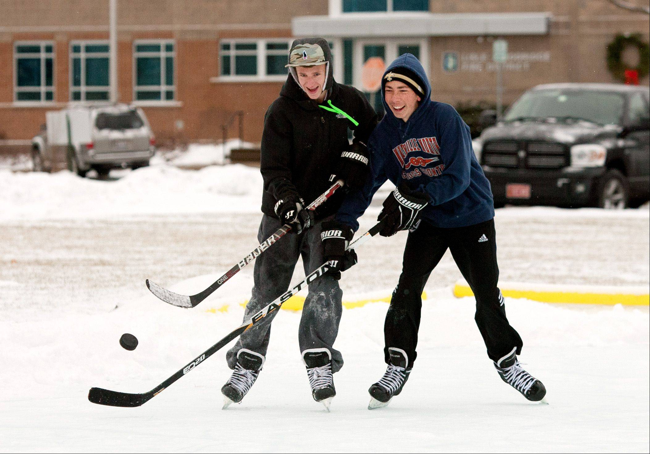 "Alex Tang, of Naperville, left, and Zach Adcock, of Woodridge, right, play hockey with their friends at a downtown outdoor Lisle ice rink off Burlington and Main Streets. Other friends playing include: Kit Benson of Naperville, Joe Lange of Naperville, and Ryan Adcock of Woodridge. ""We don't play competitive hockey, so we are just out here having fun as friends,"" said Tang."