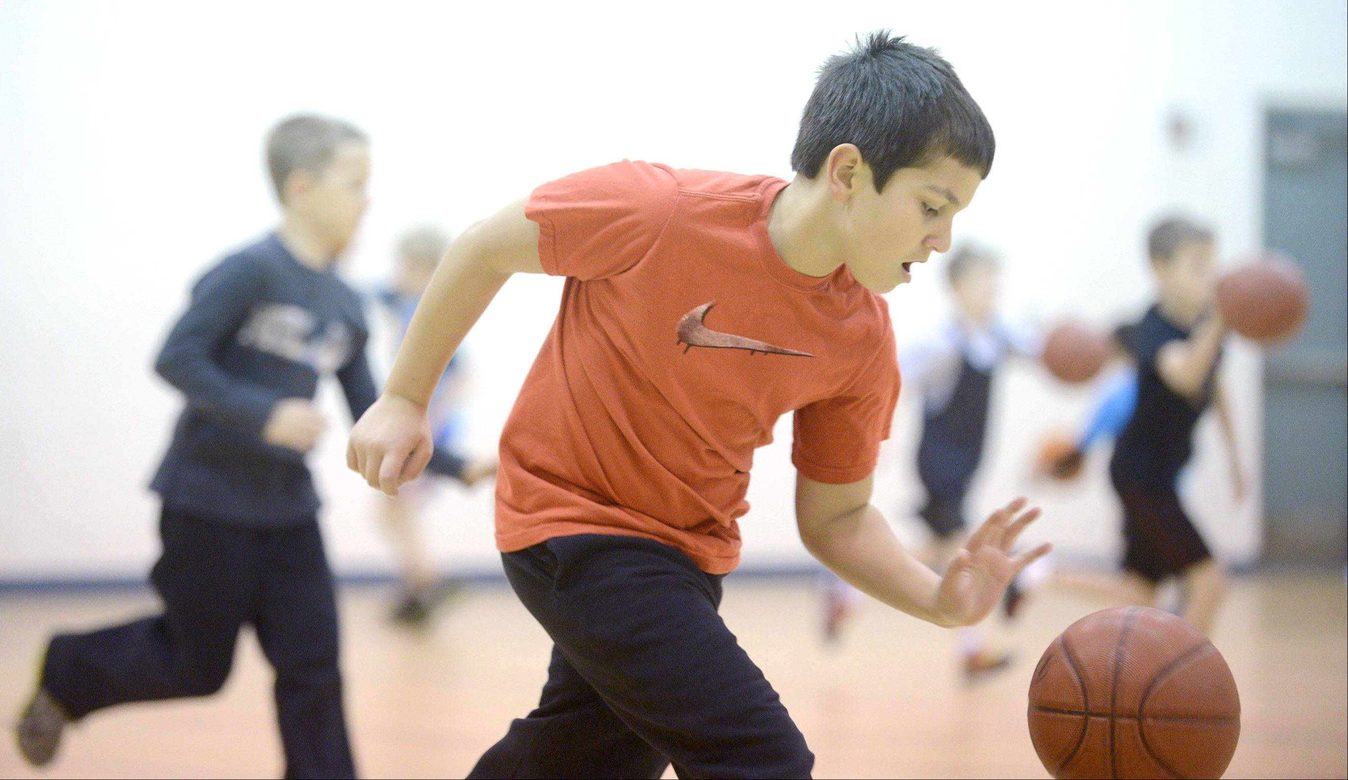 Maxx Garcia, 10, of Sugar Grove, races against fellow basketball campers during a dribbling drill at John Shields Elementary School in Sugar Grove on Thursday. The three-day park district camp, run by All Stars Sports Instruction, included basic mechanics with concentrations on shooting, ball handling, and passing.