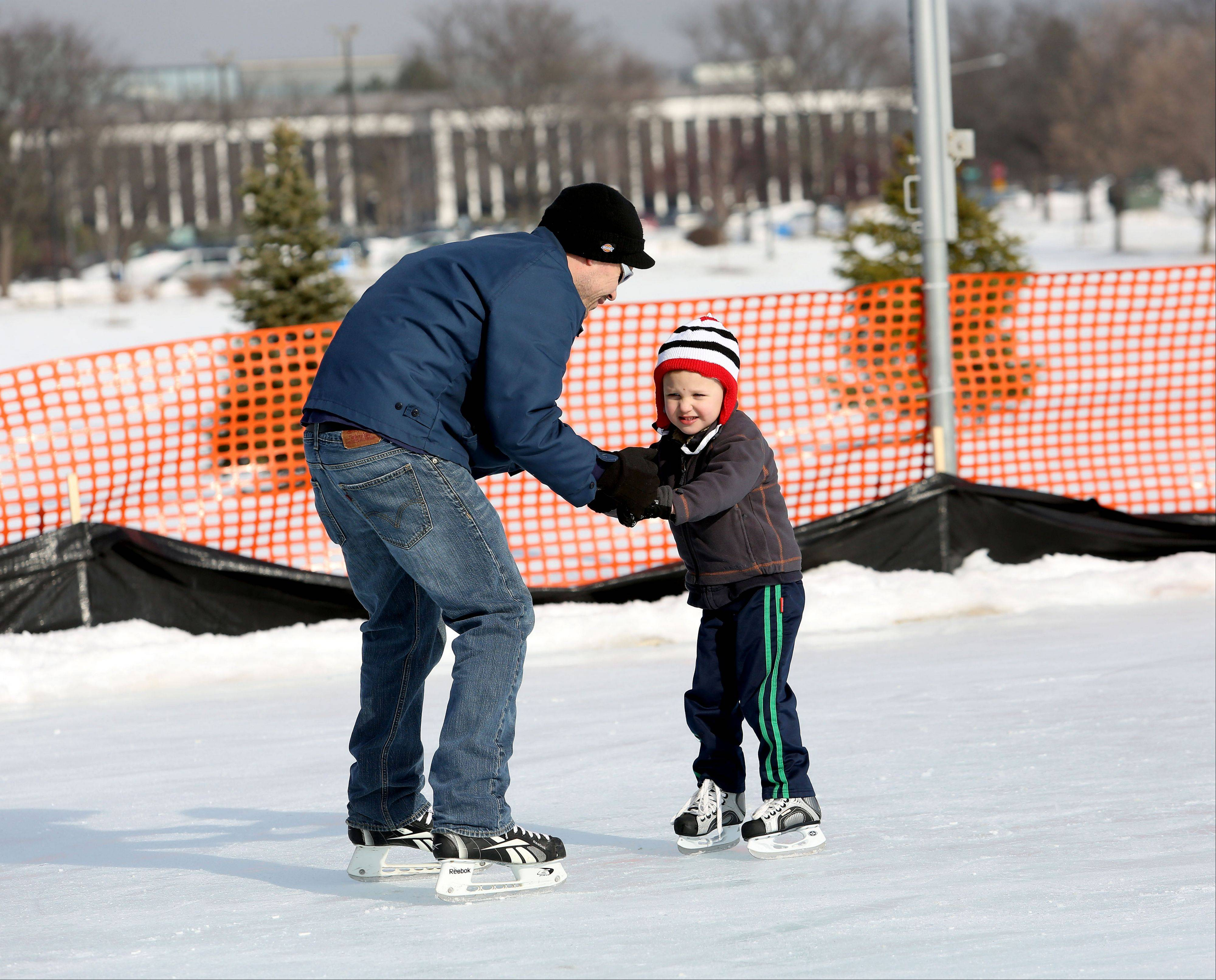 Eric Williamson helps his son Oslo, 4, around the ice rink in Nike Park in Naperville on Friday.