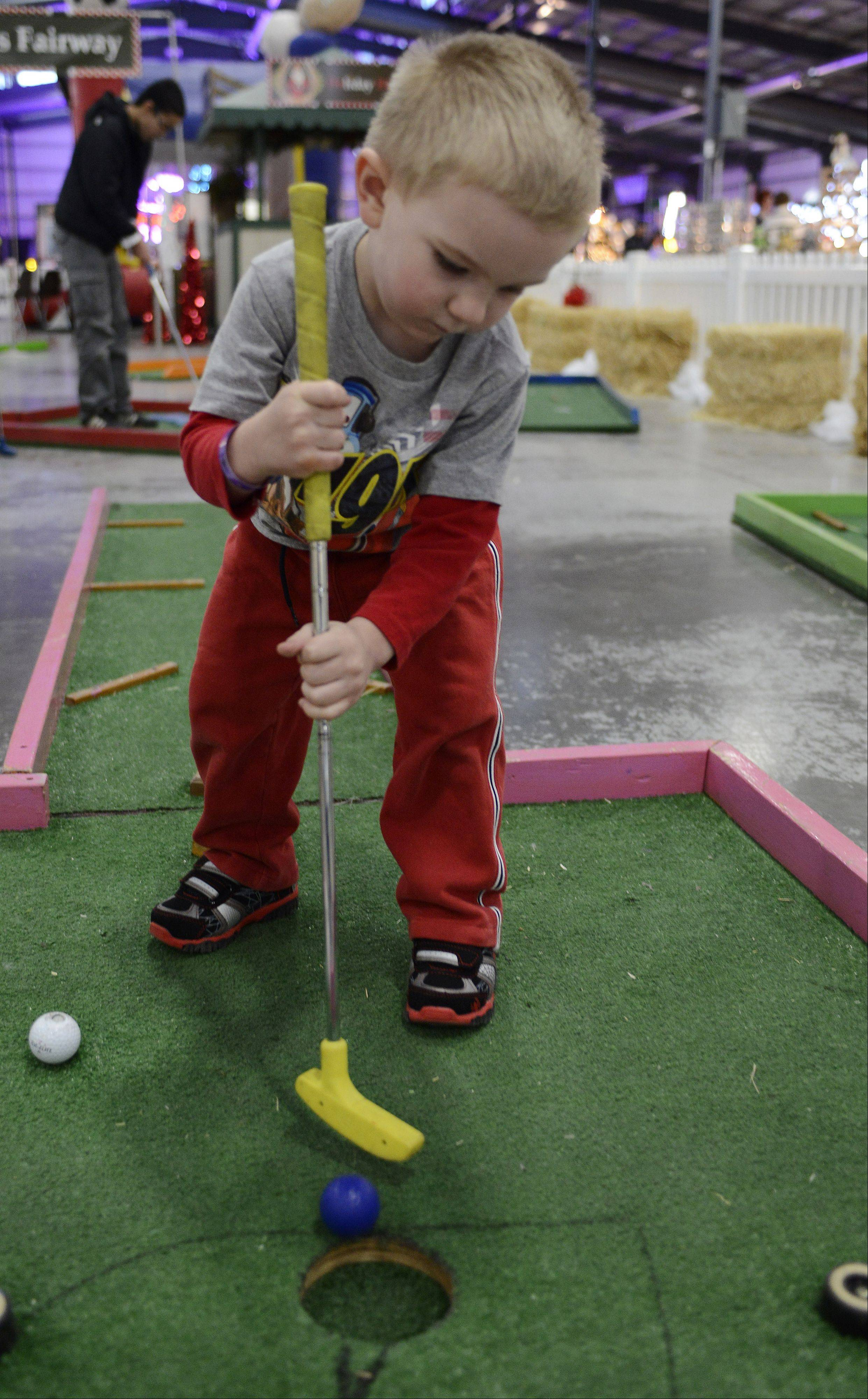 Kaiden Kohler, 3, of Rolling Meadows, plays miniature golf during the Holiday Hoedown at the Lake County Fairgrounds Saturday.