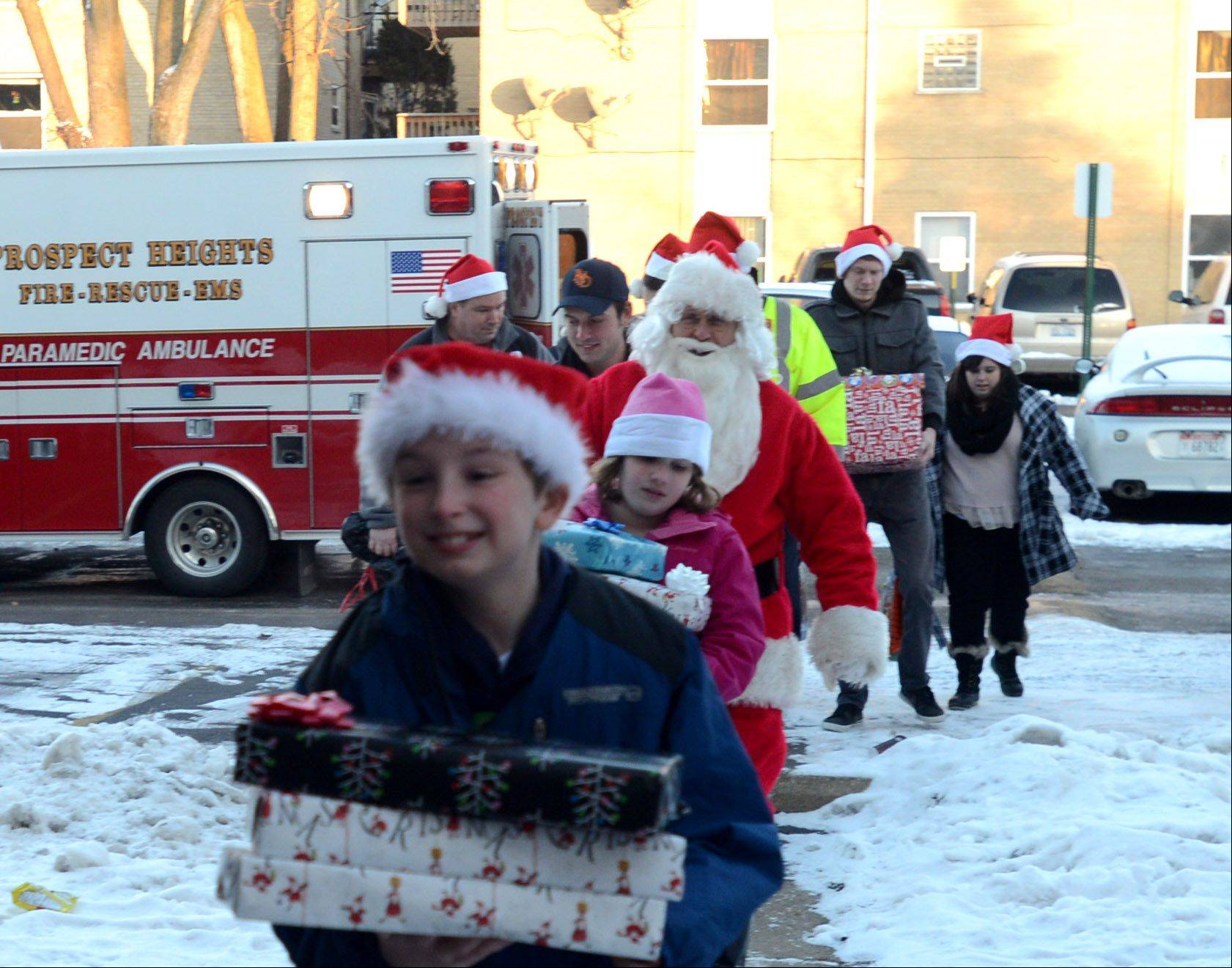 Santa Claus works with volunteers and staff of the Prospect Heights fire and police during a delivery of Christmas gifts to families of the 600 block of Piper Lane in Prospect Heights on Monday afternoon.