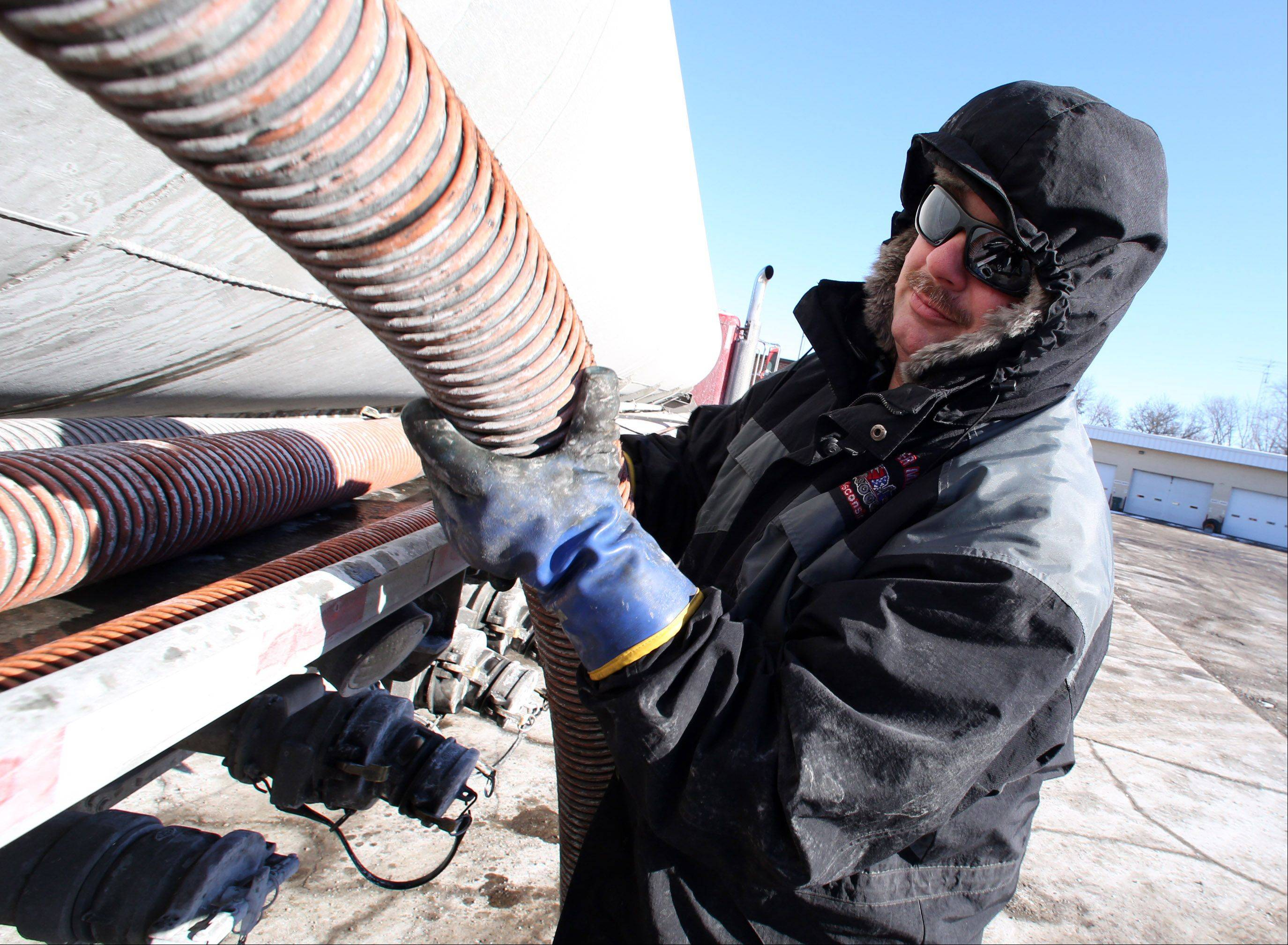 Rob Szymkowski, with Burke Transport Service in Libertyville, places a gas line hose back onto his truck after delivering diesel fuel to the Illinois Department of Transportation on Christmas Eve in Arlington Heights. Szymkowski said unloading the fuel is the coldest and most dangerous part of his job.