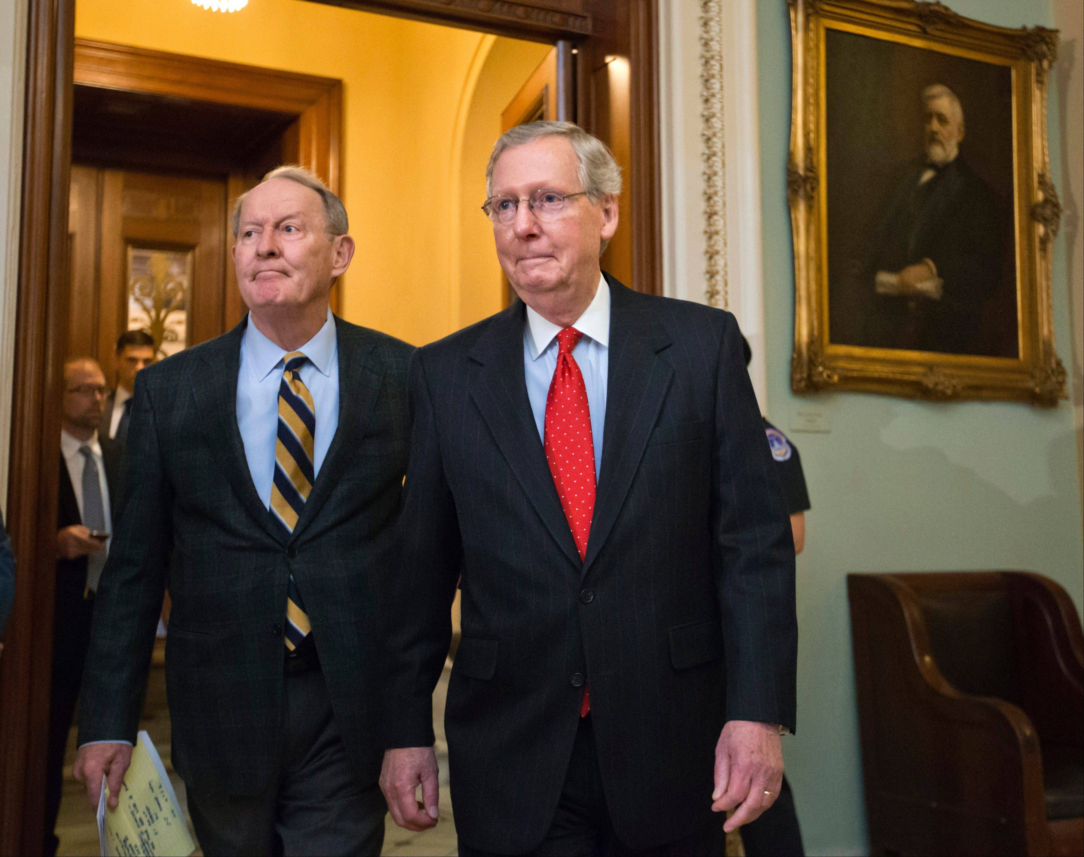 Senate Minority Leader Mitch McConnell, joined by fellow Republican Sen. Lamar Alexander of Tennessee, left, leaves the chamber to speak to reporters after the Democratic majority voted to weaken filibusters in Novemeber.