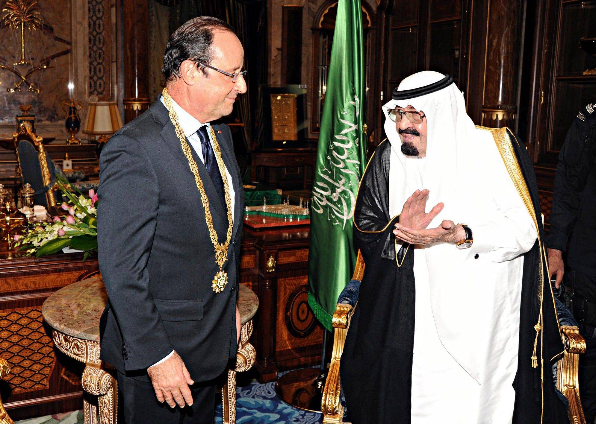 King Abdullah of Saudi Arabia, right, applauds French President Francois Hollande, left, after presenting him with the Order of Merit in Jiddah, Saudi Arabia, Nov. 4.