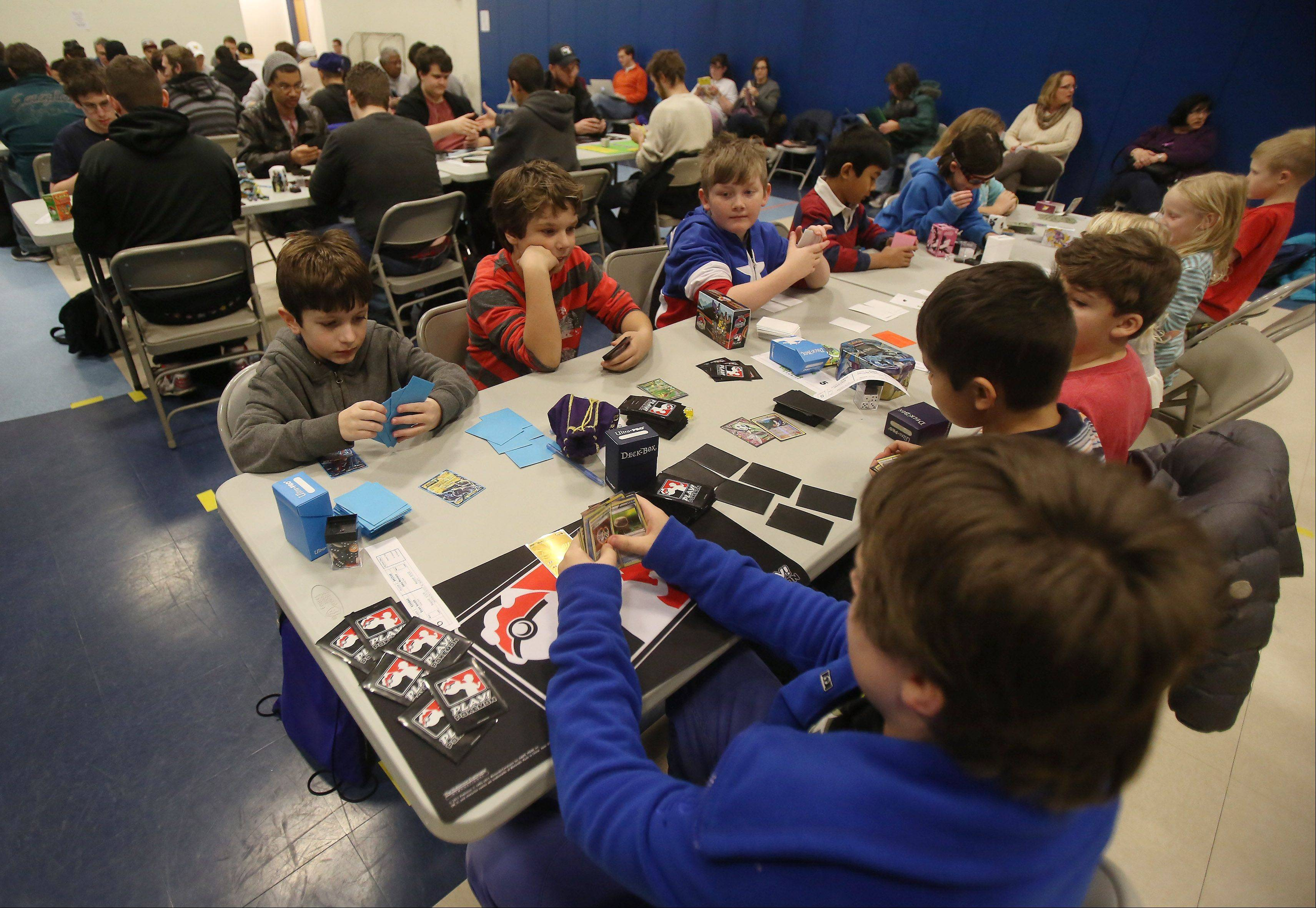 Both children and adults play during the Pokemon Trading Card Game City Championships at the Sciences and Arts Academy in Des Plaines on Sunday. The tournament attracted 89 participants from all over the Midwest, including St. Louis and Madison, Wis. Players from three age divisions competed to earn points toward a potential invitation to the 2014 Pokemon World Championships in Washington, D.C., next summer.