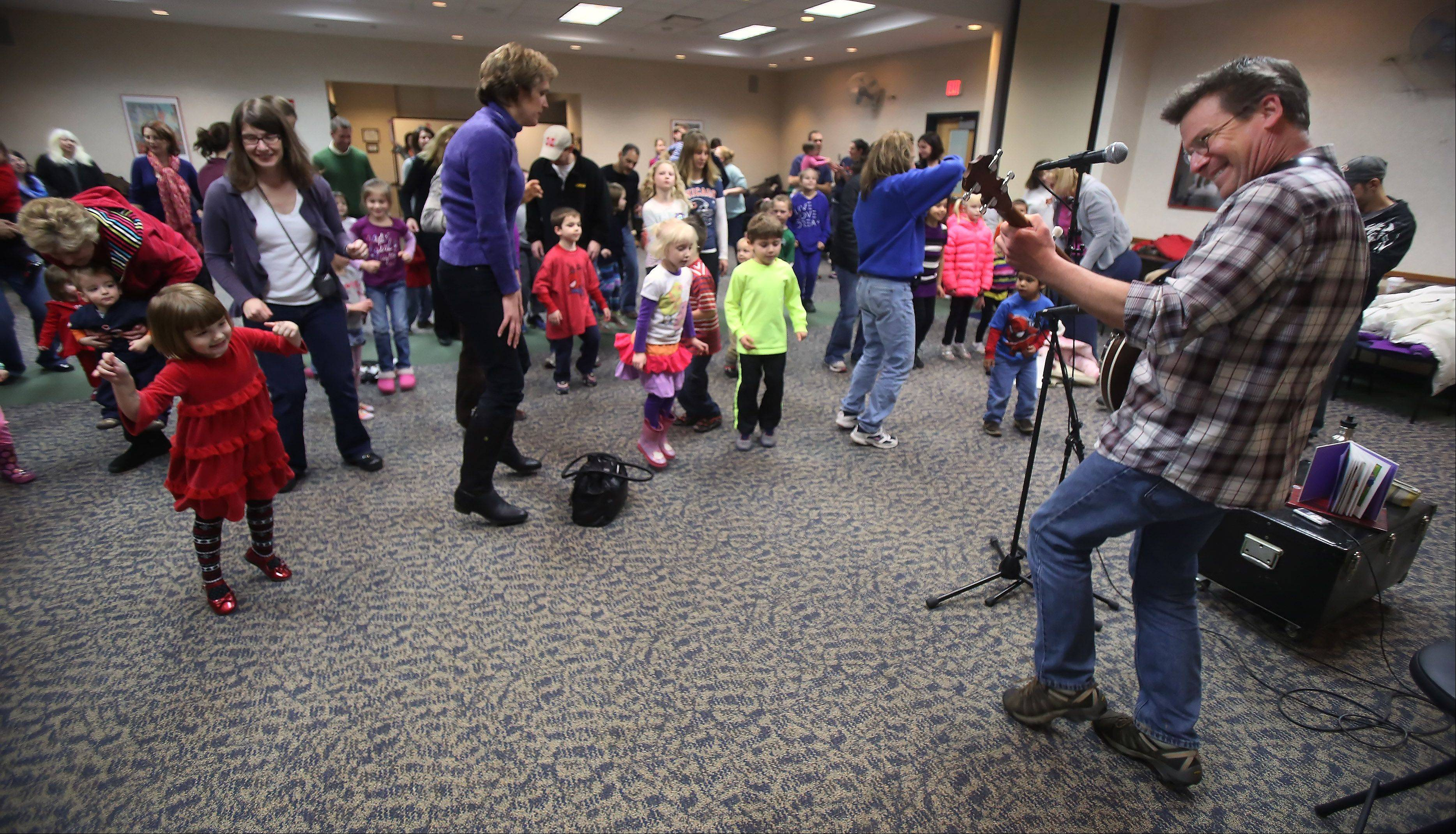 "Musician Jim Gill entertained families during a ""Sing in the New Year"" concert Sunday at Fremont Public Library in Mundelein. An audience of about 100 clapped, danced and sang to the music of Gill as he played his banjo."