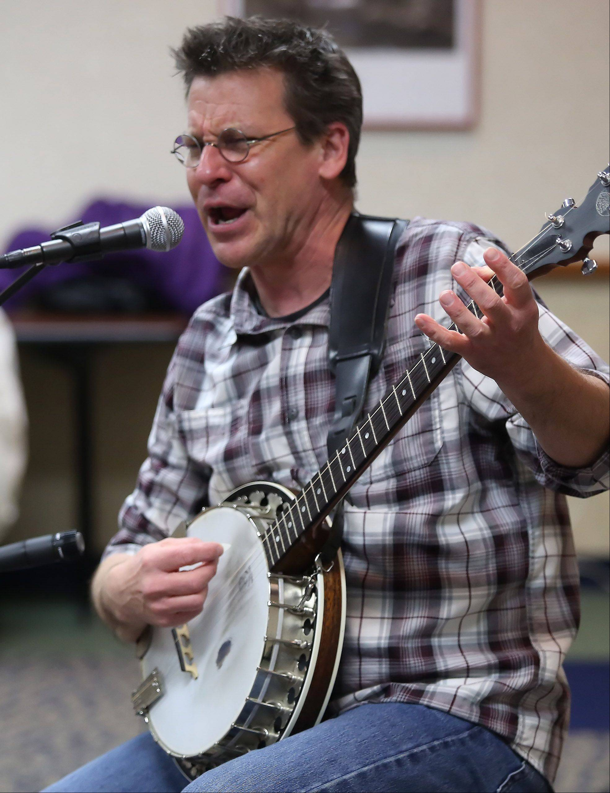 "Musician Jim Gill entertains kids and their parents Sunday during a ""Sing in the New Year"" concert y at Fremont Public Library in Mundelein. About 100 audience members clapped, danced and sang along with Gill as he played his banjo."