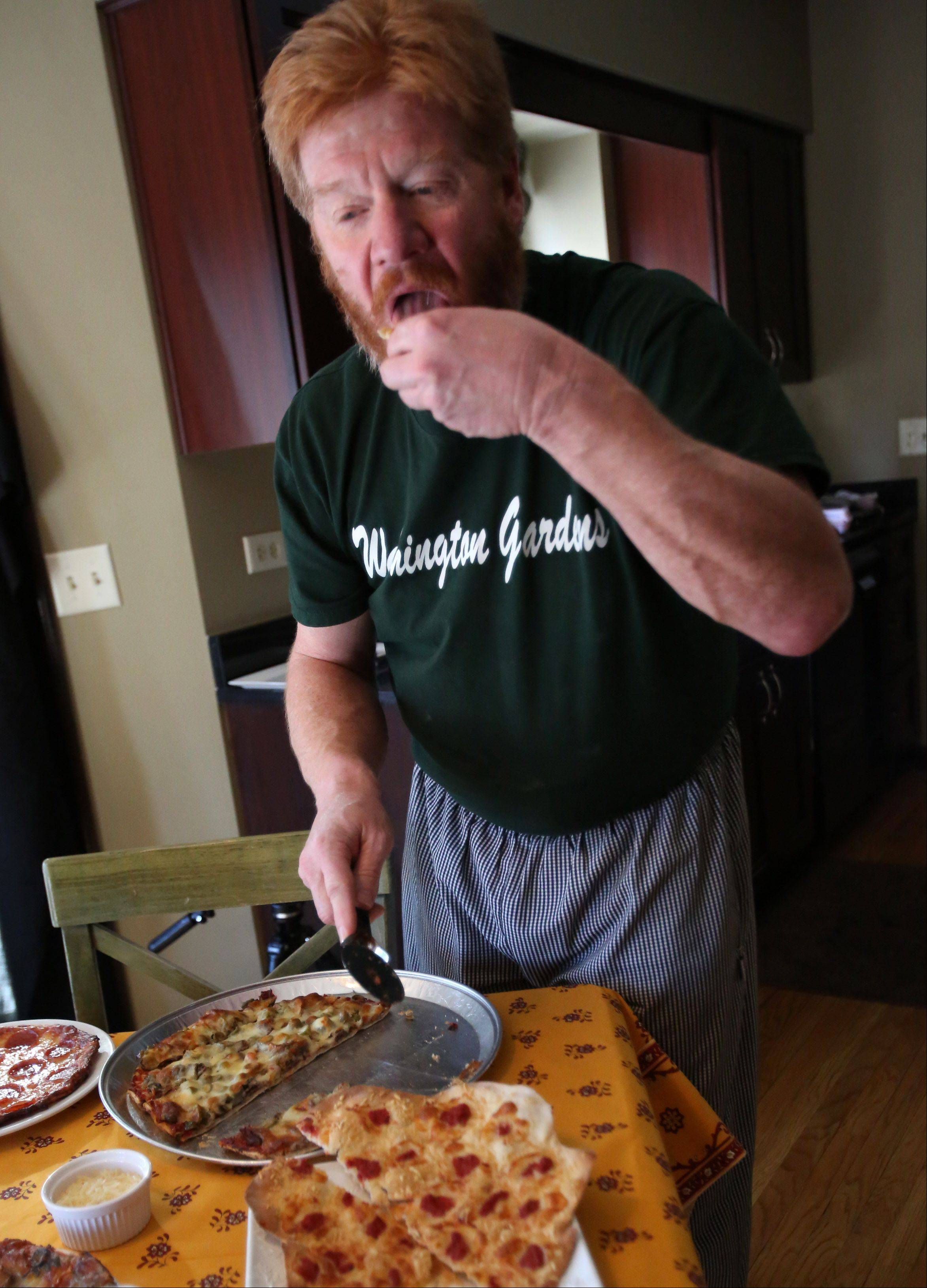 "Jim Stoecker takes a bite of pizza he made at his home in Long Grove. Stoecker is the ""Keeper of The Flame"" and owner of Alex's Washington Gardens in Highwood."
