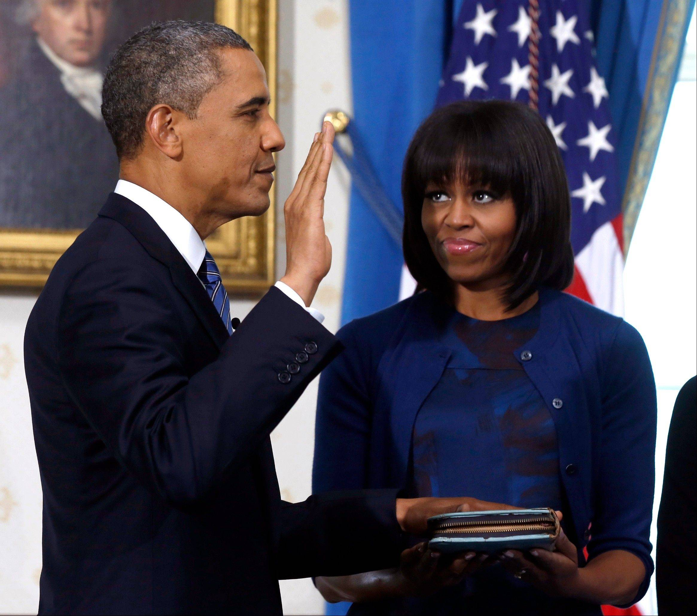 President Barack Obama is officially sworn in by Chief Justice John Roberts, not pictured, on Jan. 20 in the Blue Room of the White House in Washington as first lady Michelle Obama, holds the Robinson family Bible.