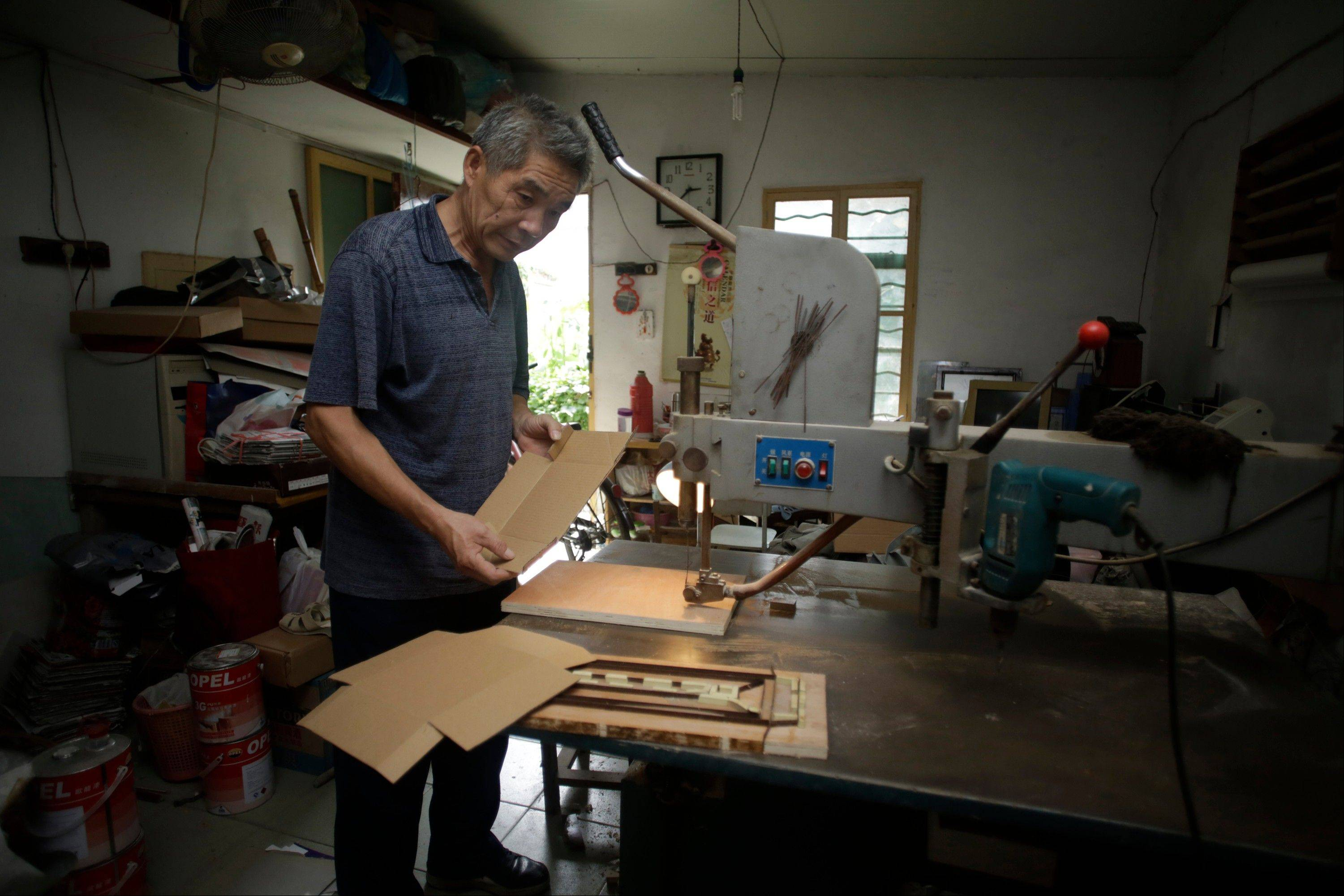 Dong Linhua, 59, works at his workshop in Shanghai, China. Dong, who worked in a state-owned clothing company while later being laid off, started a workshop that produces the molds of the paper box for the factories. He does not have a job now.