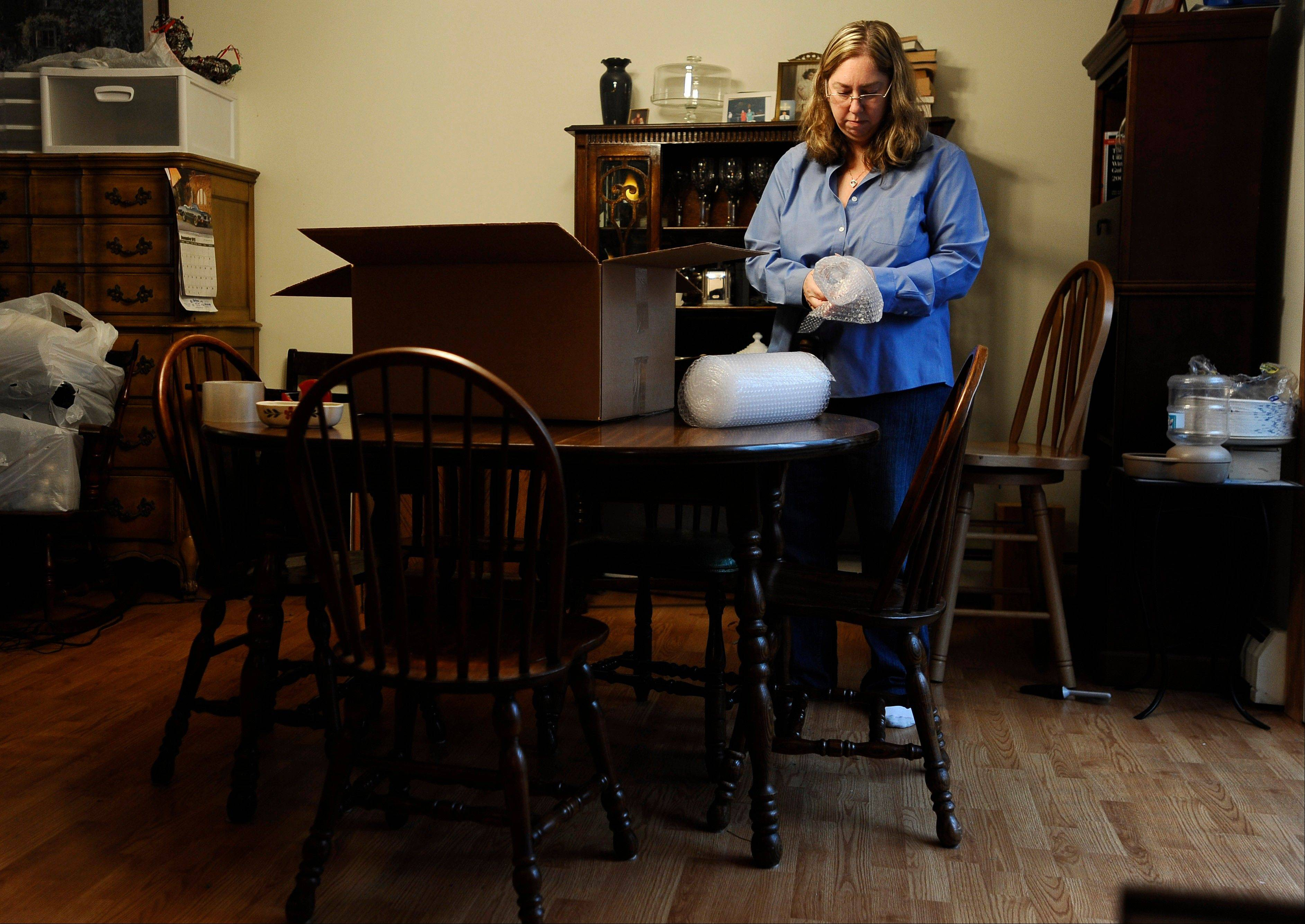 Leslie Lynch packs up belongings in her dining room in Glastonbury, Conn. Lynch, who lost her job last year, is moving out of her home of 21 years because she can no longer afford the mortgage payments.