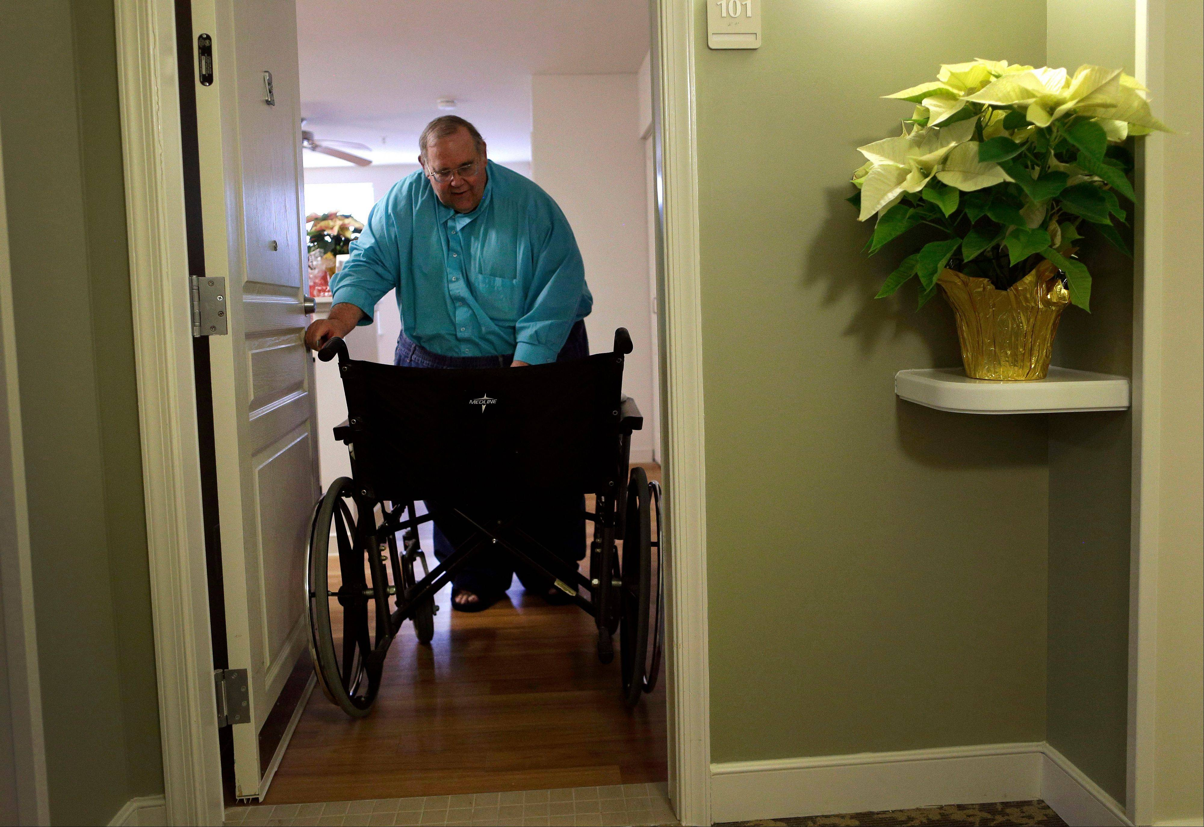 George Warren pulls his wheelchair through his apartment's front door at Village Crossroads, an affordable senior community in Nottingham, Md. Warren's wheelchair is too wide for the doorway and he can't afford a narrower model, so he folds it before carefully pulling it through.