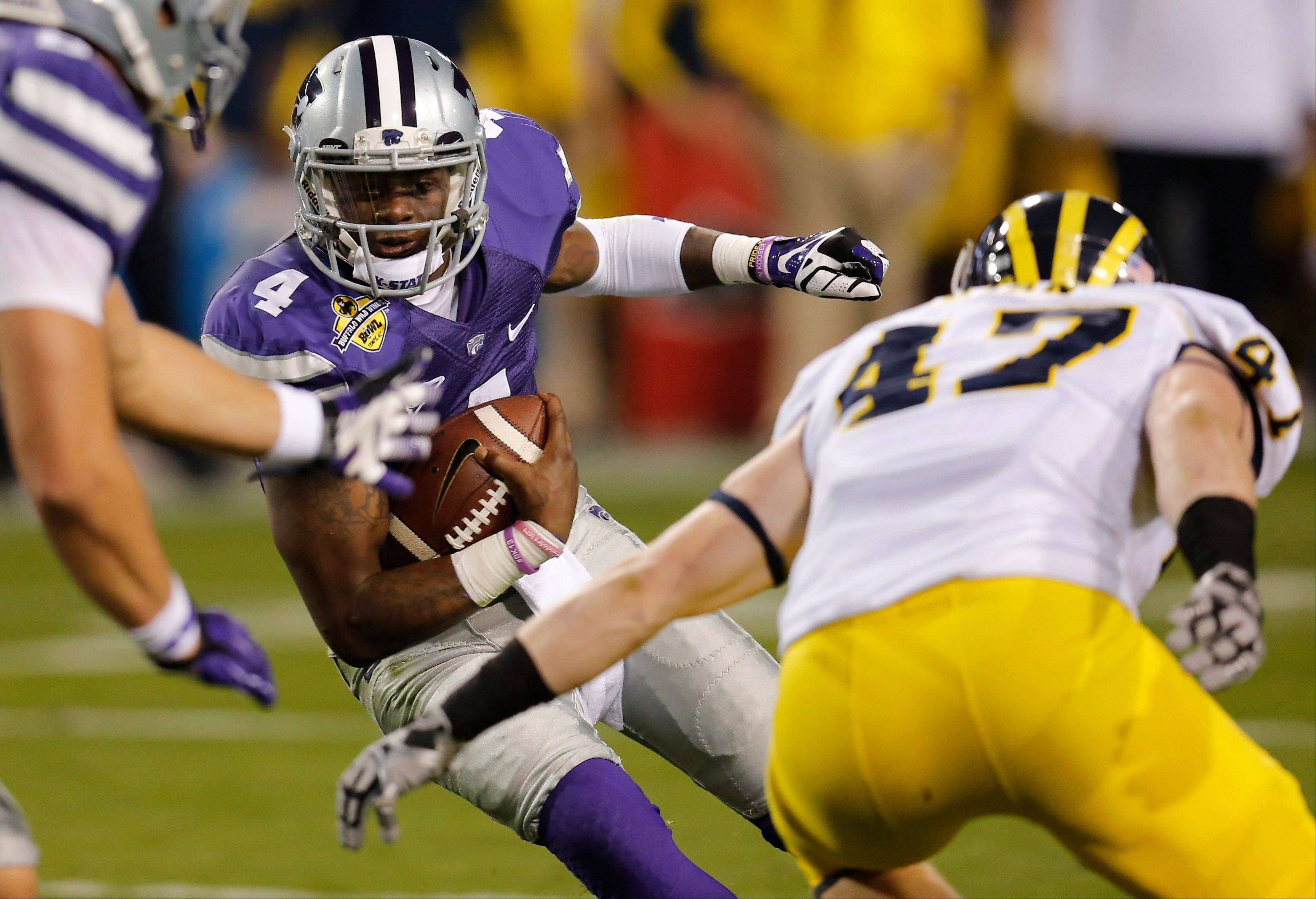 Kansas State quarterback Daniel Sams (4) scrambles as Michigan linebacker Jake Ryan (47) defends during the first half of the Buffalo Wild Wings Bowl NCAA college football game on Saturday, Dec. 28, 2013, in Tempe, Ariz.