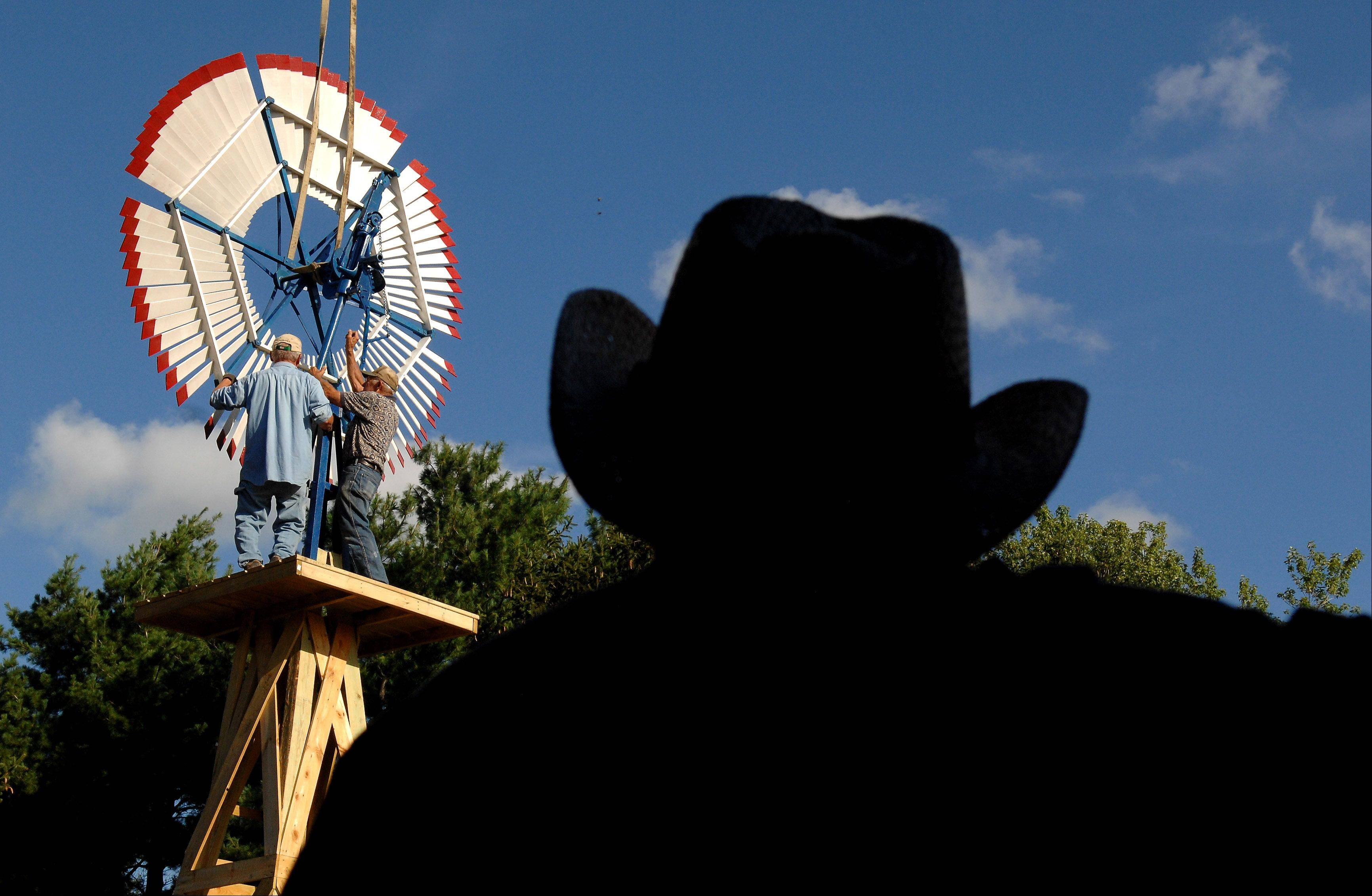 Jim Turner watches as Frank Engel, right on the windmill, and Bill Chidester work on installing a windmill at the top of a 25-foot tower at Turner's farm in Garden Prairie.