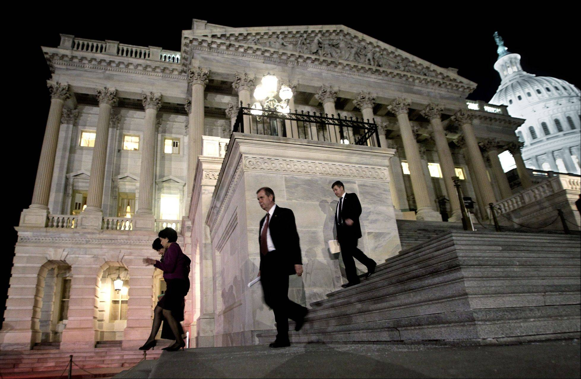Congressmen walk down the steps of the House of Representatives as they work throughout the night on a spending bill, on Capitol Hill in Washington.