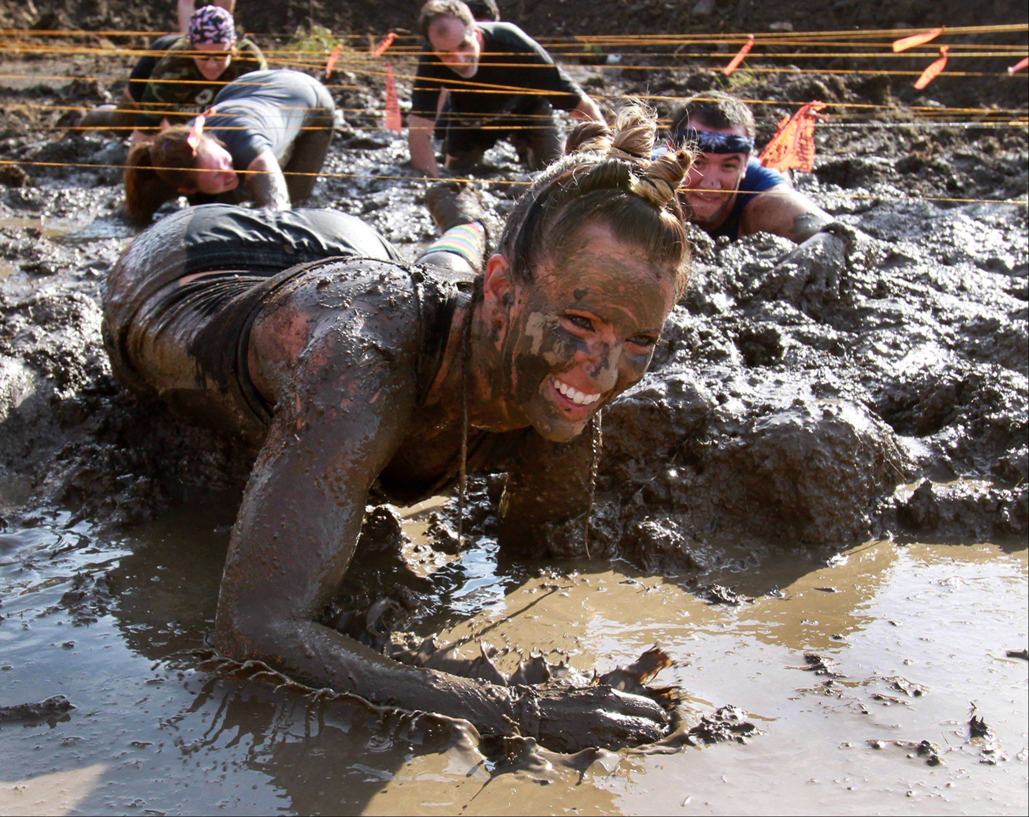 Allison Barton of Elk Grove Village crawls in mud during the Eat Dirt Mud Run at Willow Creek Community Church in South Barrington in September.