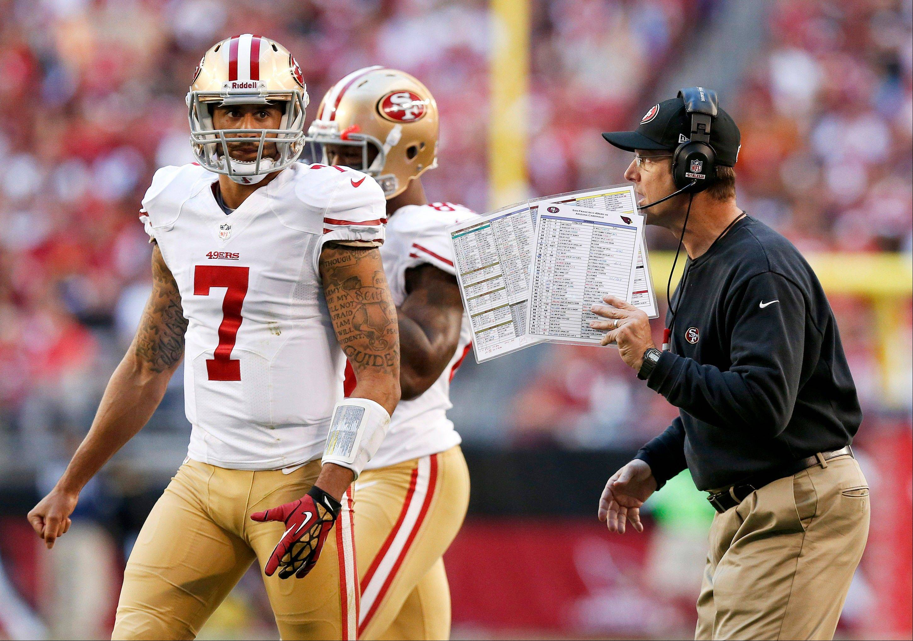 San Francisco 49ers head coach Jim Harbaugh, right, talks with quarterback Colin Kaepernick prior to a play during the first half of Sunday�s road game against the Arizona Cardinals. The 49ers will be back on the road for their first-round playoff game.