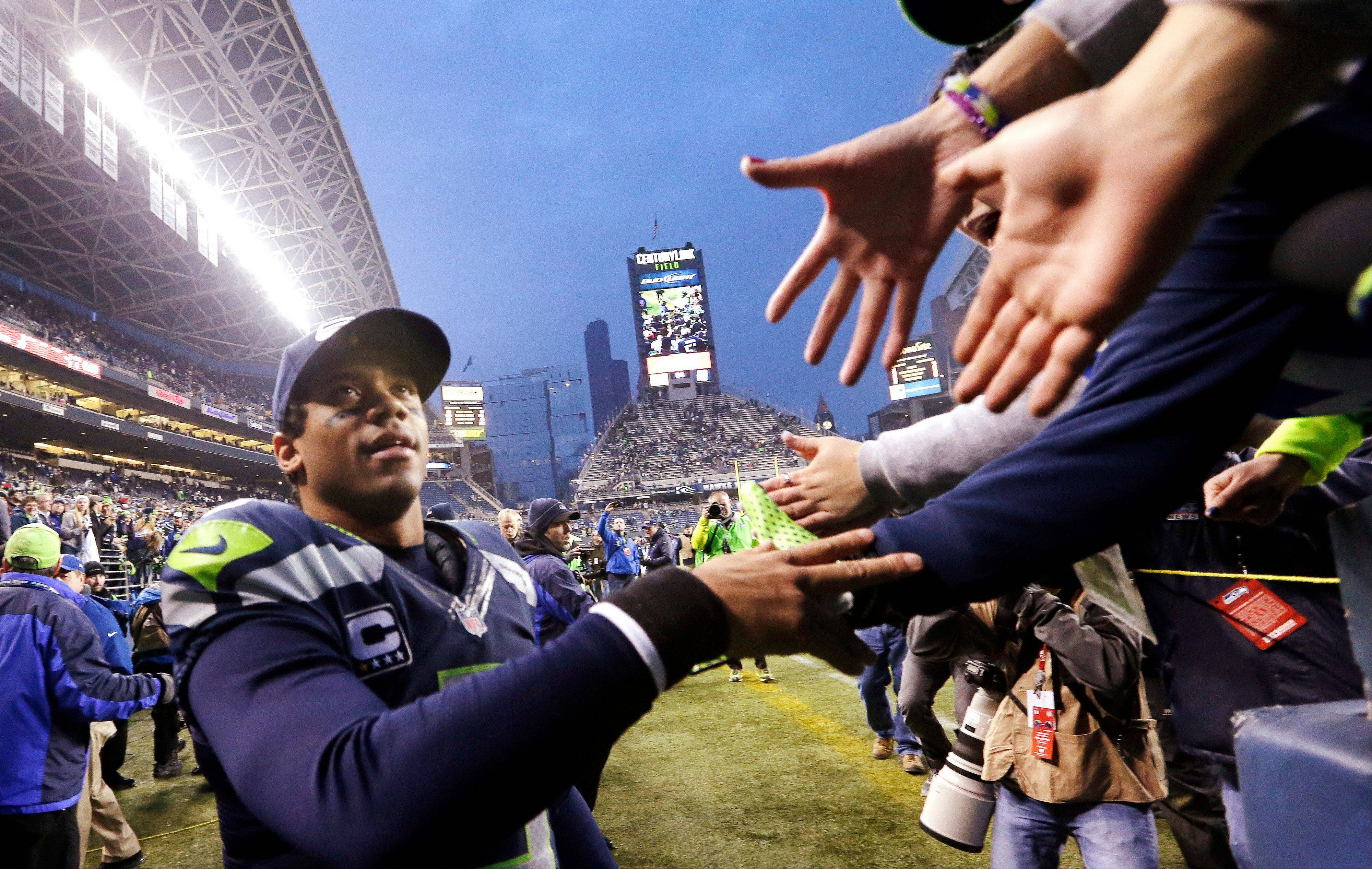 Seahawks quarterback Russell Wilson greets fans as he leaves the field after the team beat the St. Louis Rams on Sunday in Seattle.