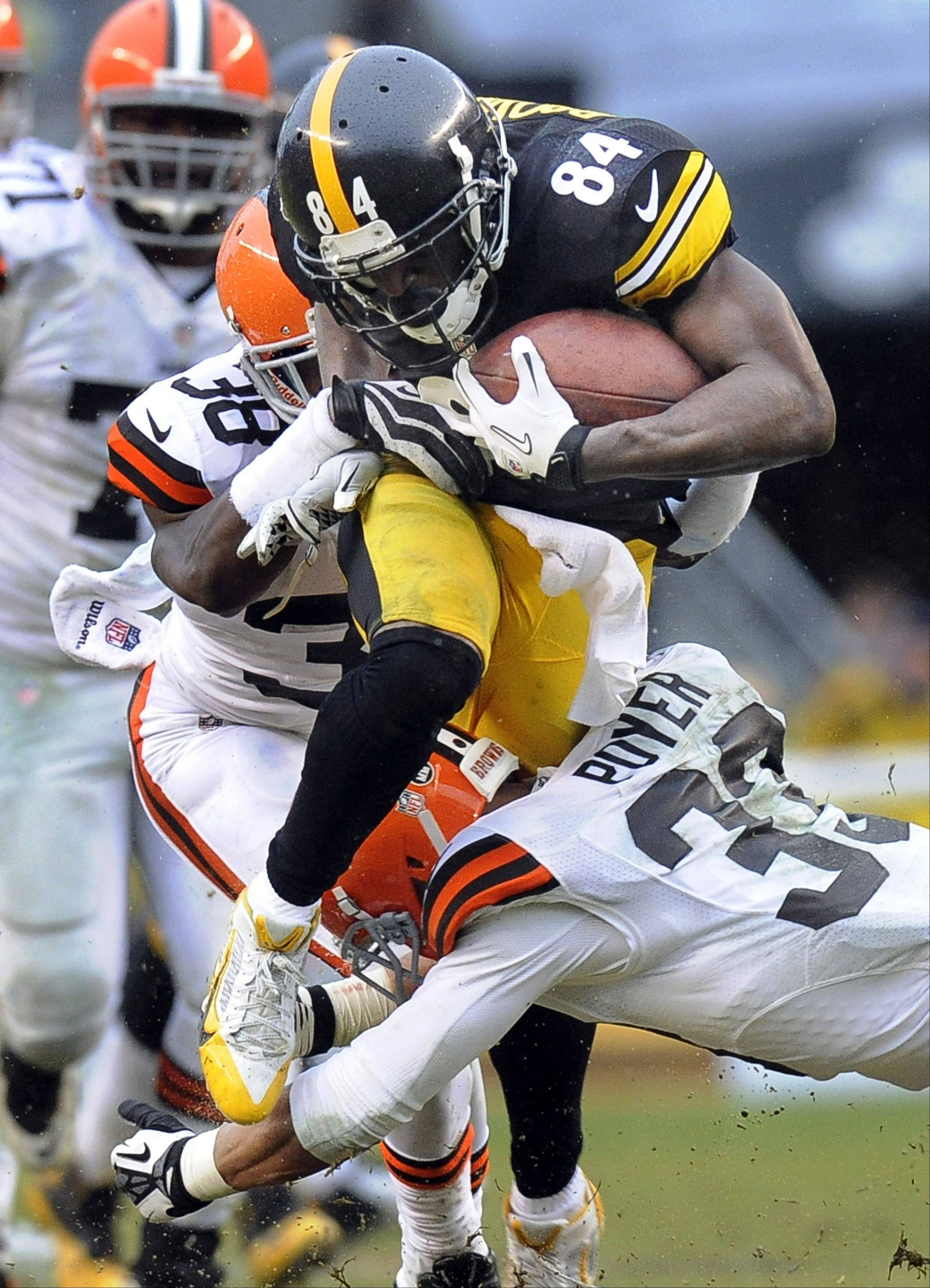 Steelers wide receiver Antonio Brown tries to break through a tackle by Cleveland Browns defensive back Julian Posey in the third quarter of Sunday�s game in Pittsburgh.
