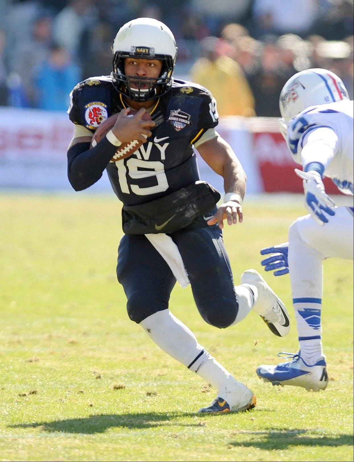 Navy quarterback Keenan Reynolds runs upfield past Middle Tennessee Blue Raiders defensive end Raynard Felton in the first half of the Armed Forces Bowl on Monday in Fort Worth, Texas.