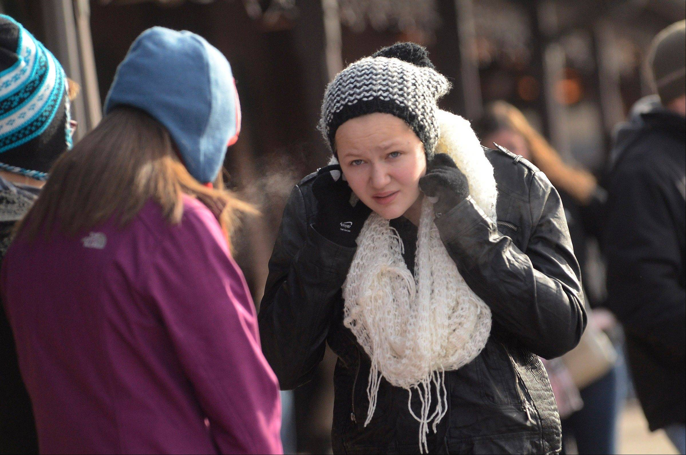 Julia Skwerski bundles up while waiting for a train at the Arlington Heights Metra Station with her mom and sister who are en route to the Walnut Room inside Macy's in downtown Chicago. Weather forecasters say snow will join the frigid temperatures beginning Tuesday afternoon and continuing possibly to Wednesday evening.