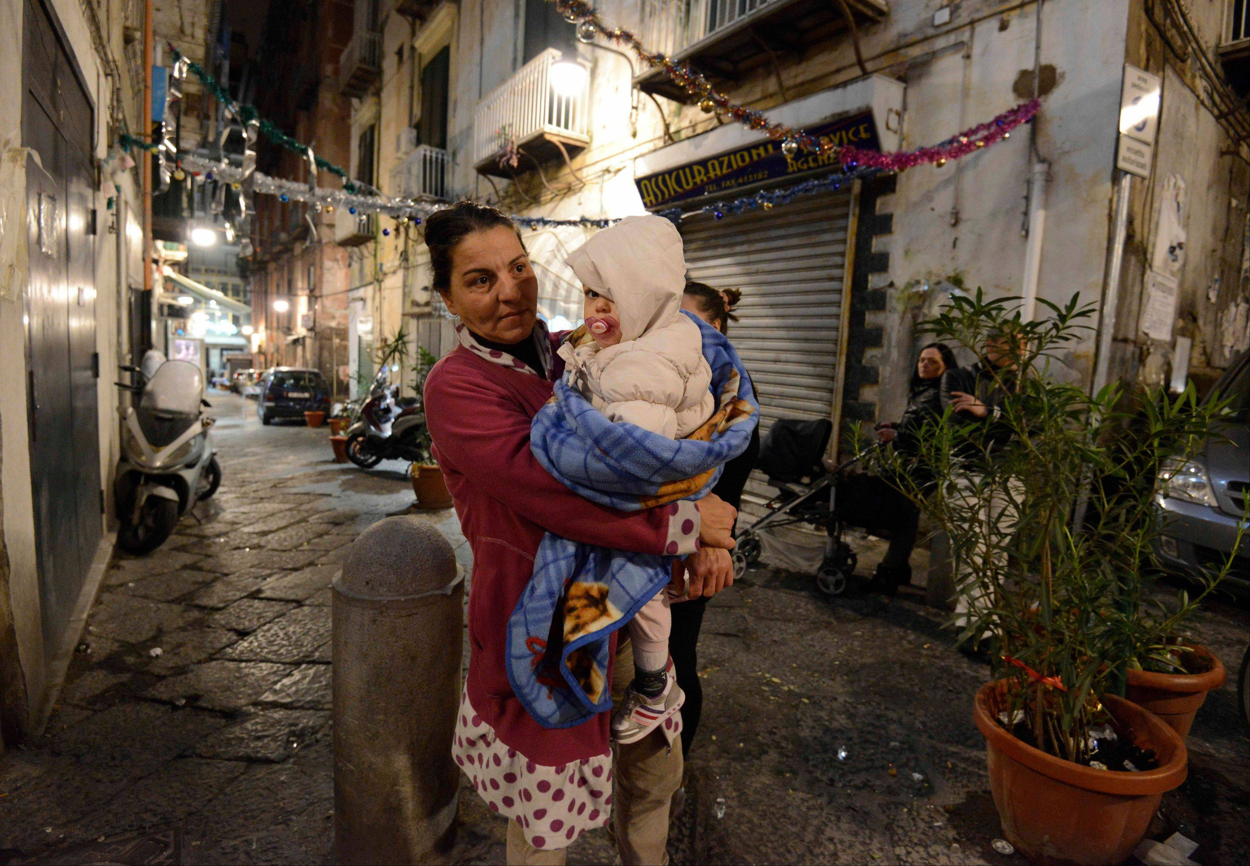 A woman holds a child wrapped in a blanket as she stands on a street in Naples, Italy, Sunday.