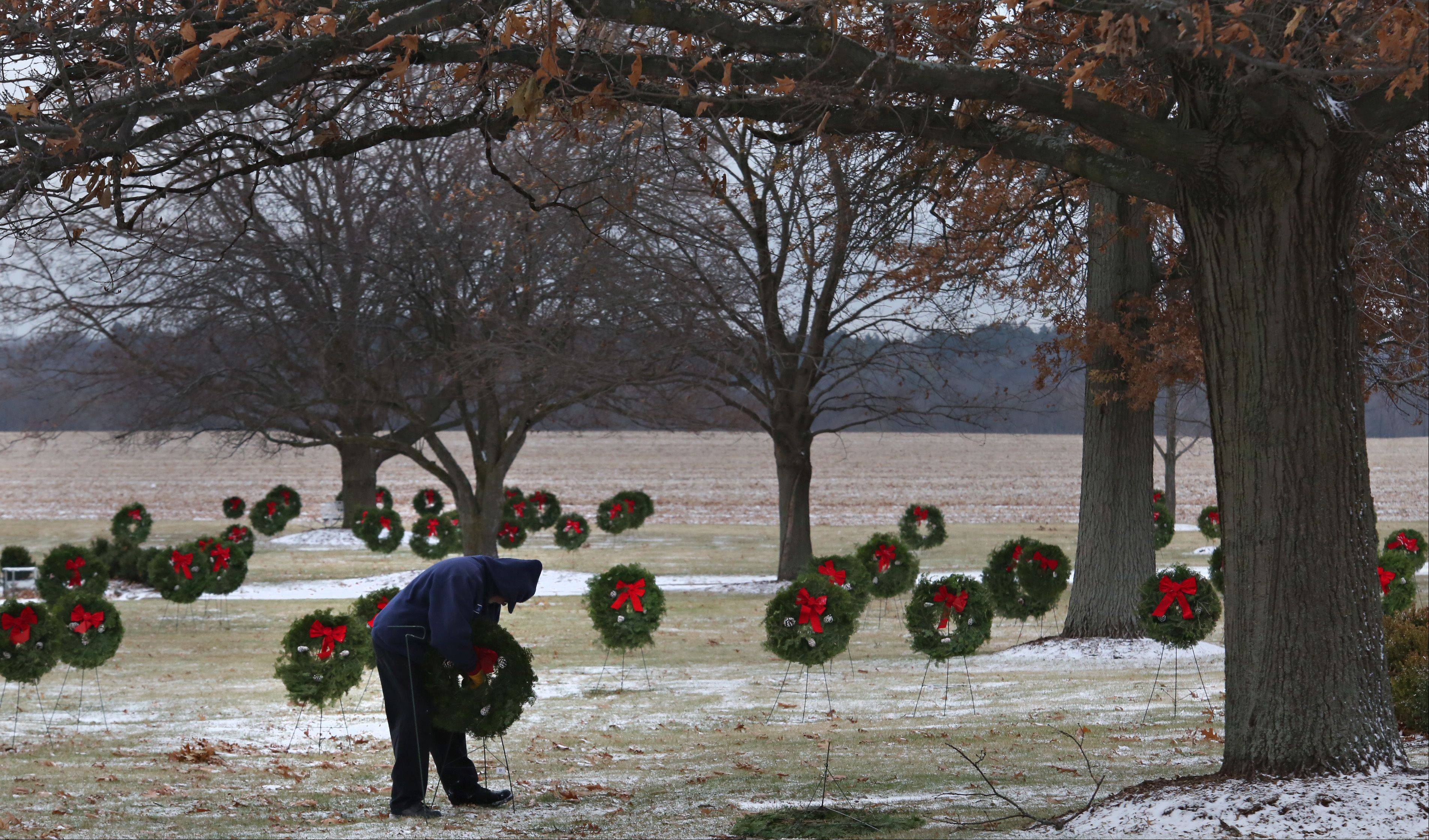 Jim Erboe, a part-time employee at River Valley Memorial Gardens in West Dundee places Christmas wreaths on the graves of veterans buried at the picturesque cemetery.