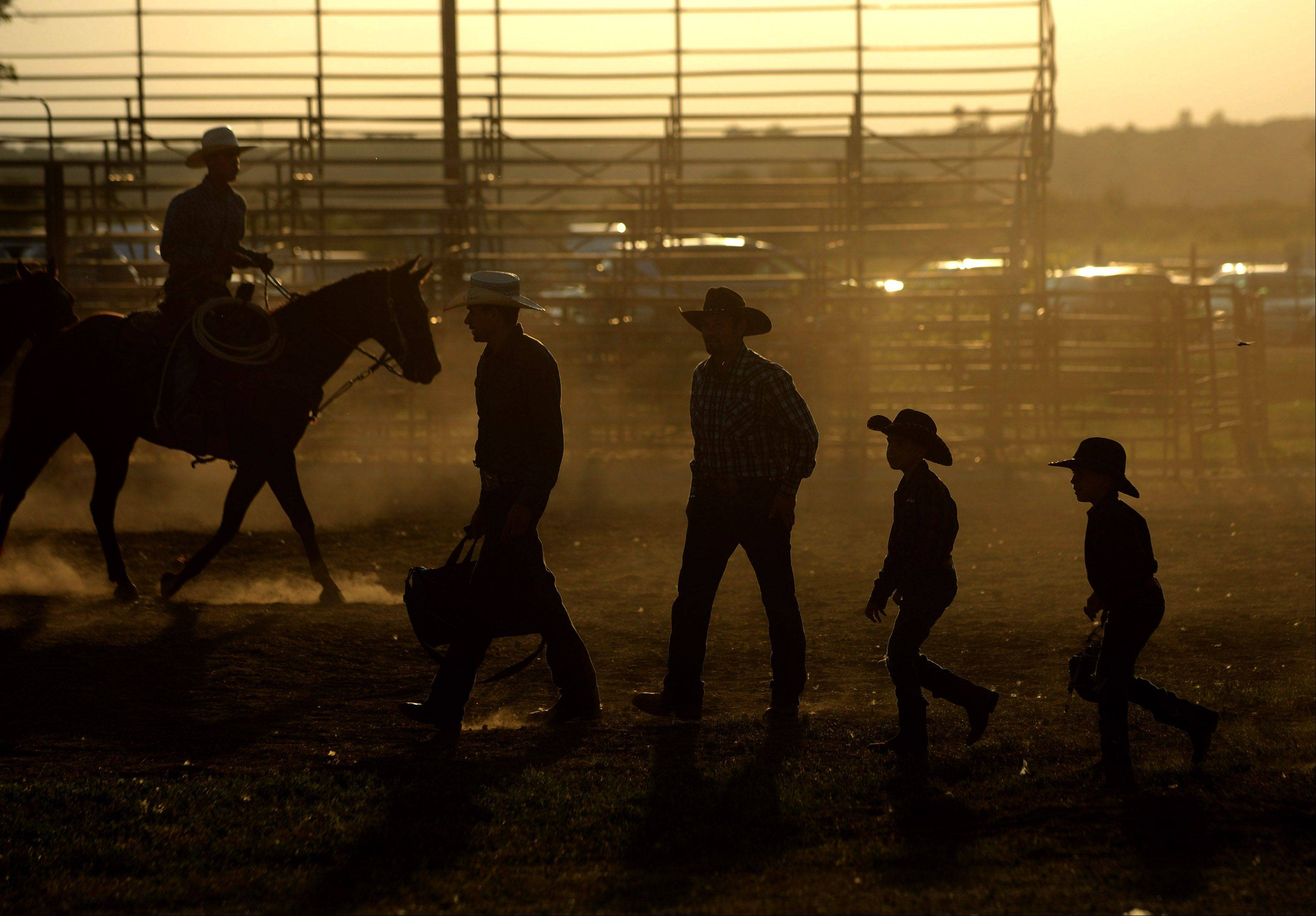 I admit that I'm a sucker for several photographic clich�s. So when I saw the combination of golden light from the setting sun and silhouettes of people in cowboy hats before the Championship Bull Riding event at the Kane County Fair in St. Charles, I couldn't help myself. There are worse tropes I suppose. Right? PERSPECTIVE is a weekly