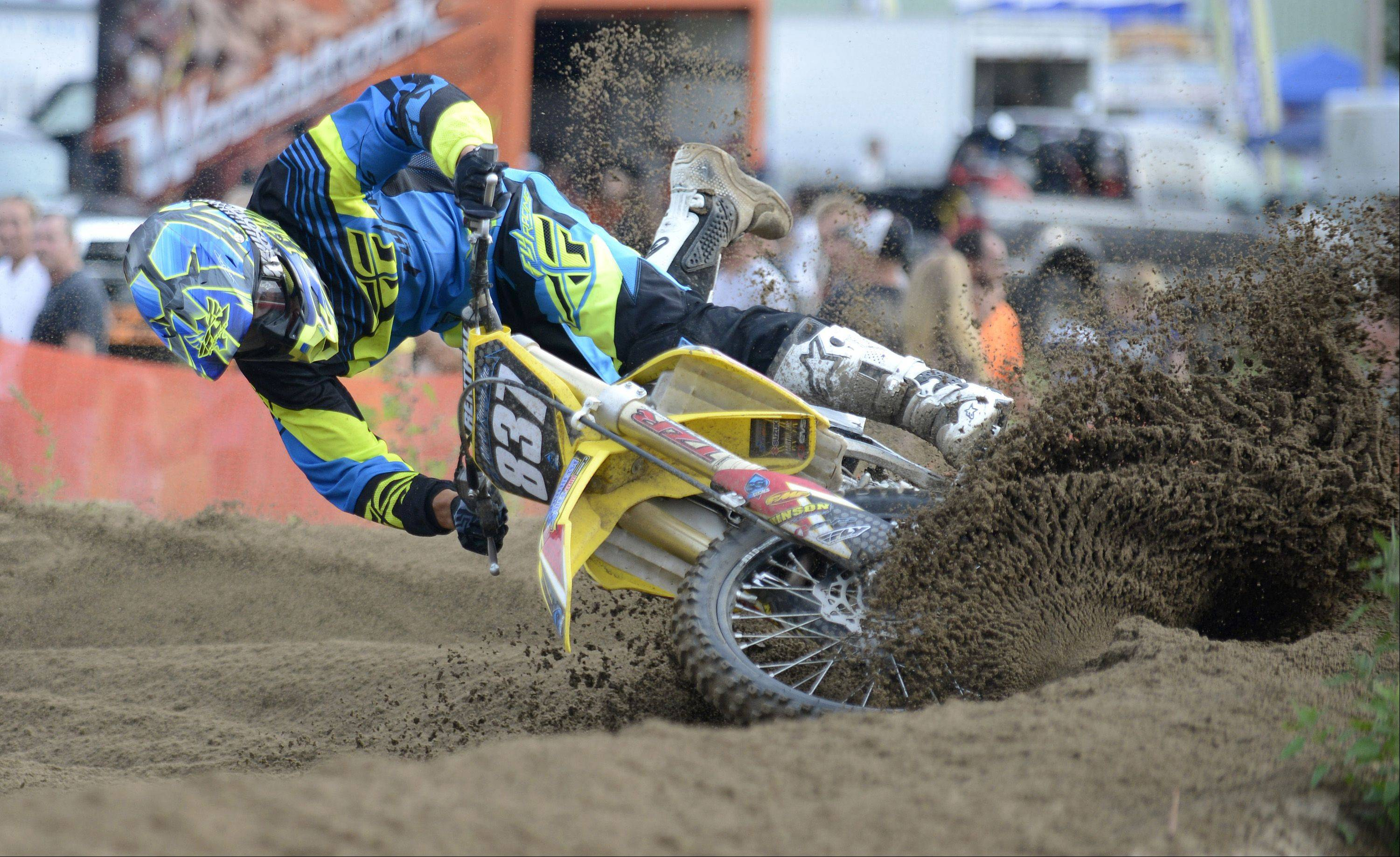 Ross Martin, 28, of Burlington, WI, tips his bike in the deep dirt of a bend and loses his first place lead in the 250 A class race at the motocross racing event at the McHenry County Fair in Woodstock on Friday, August 2. Martin has been racing since he was nine years old.