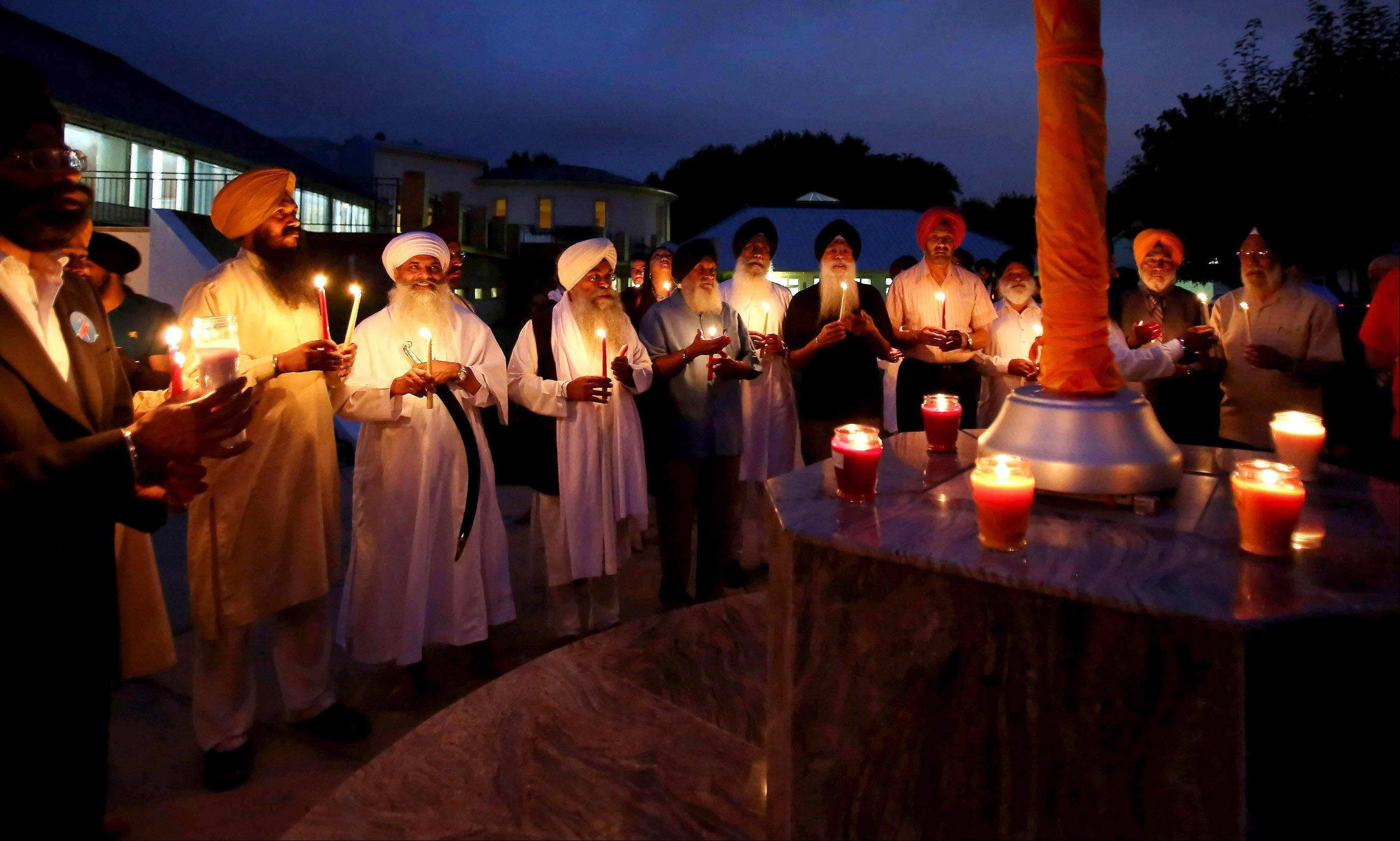 Members of the Gurudwara of Palatine hold a vigil to honor victims of the shooting at a Sikh temple in Milwaukee.