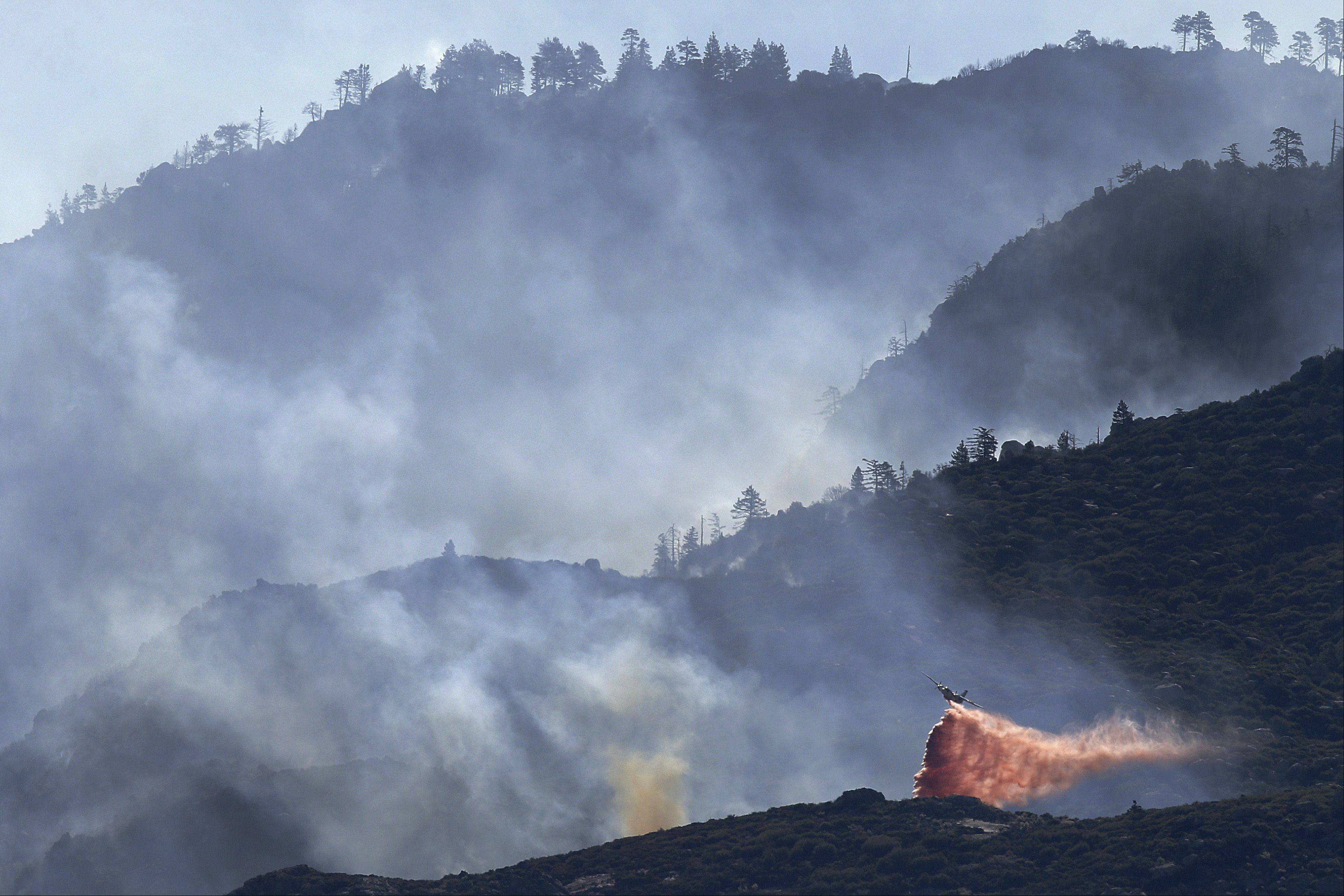 An air tanker drops fire retardant on a hot spot as firefighters continue to battle a wildfire on Friday, Aug. 9, 2013, near Banning, Calif.
