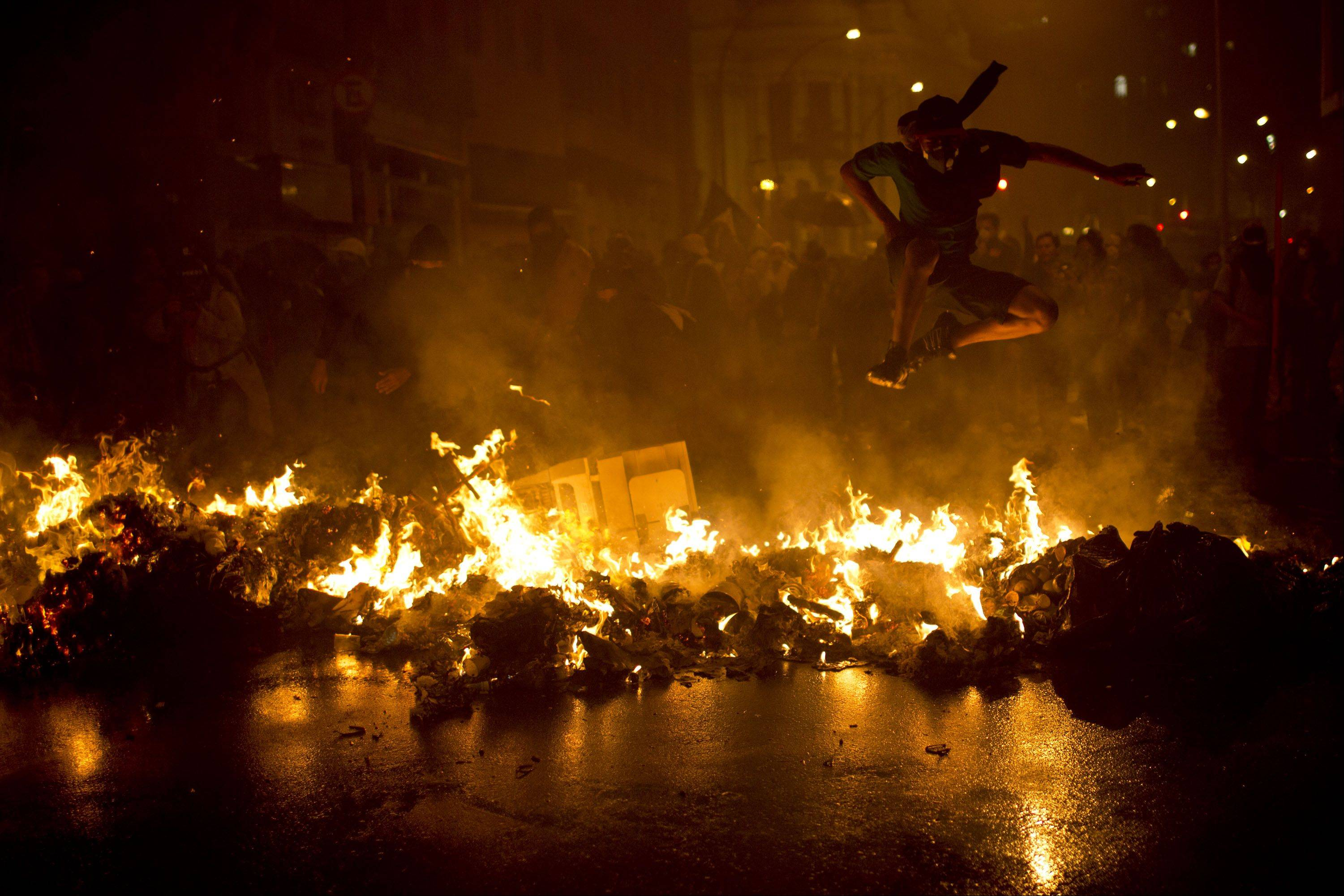 A demonstrator with his face covered jumps over a burning barricade at the Cinelandia square during a march in support of teachers on strike in Rio de Janeiro, Brazil, Monday, Oct. 7, 2013. Teachers have been on strike demanding better pay for almost two months.