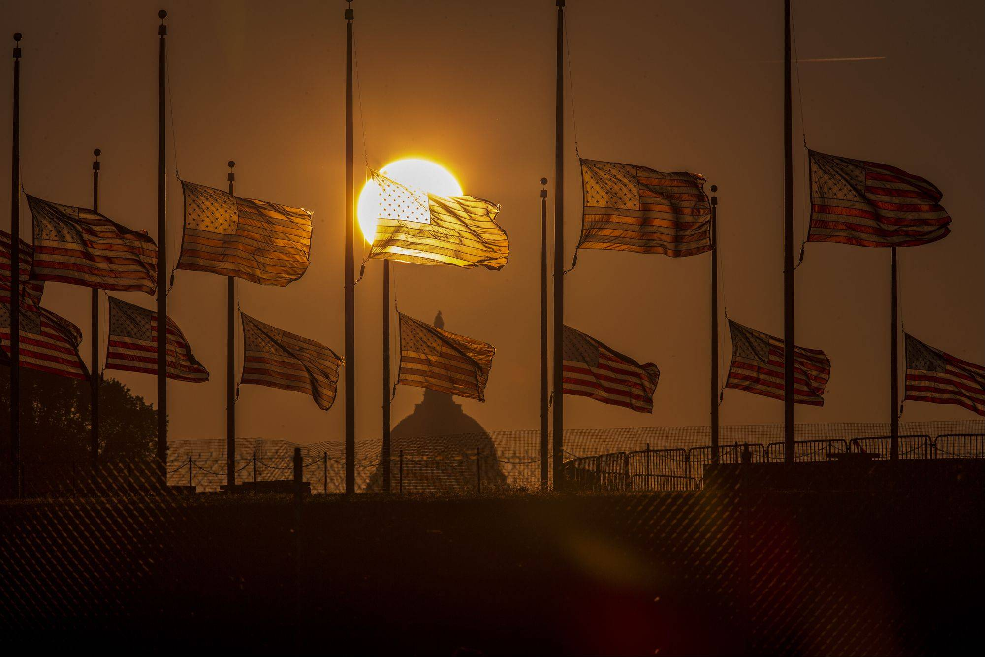 The flags surrounding the Washington Monument fly at half-staff as ordered by President Barack Obama following the deadly shooting Monday at the Washington Navy Yard, Tuesday morning, Sept. 17, 2013, in Washington.