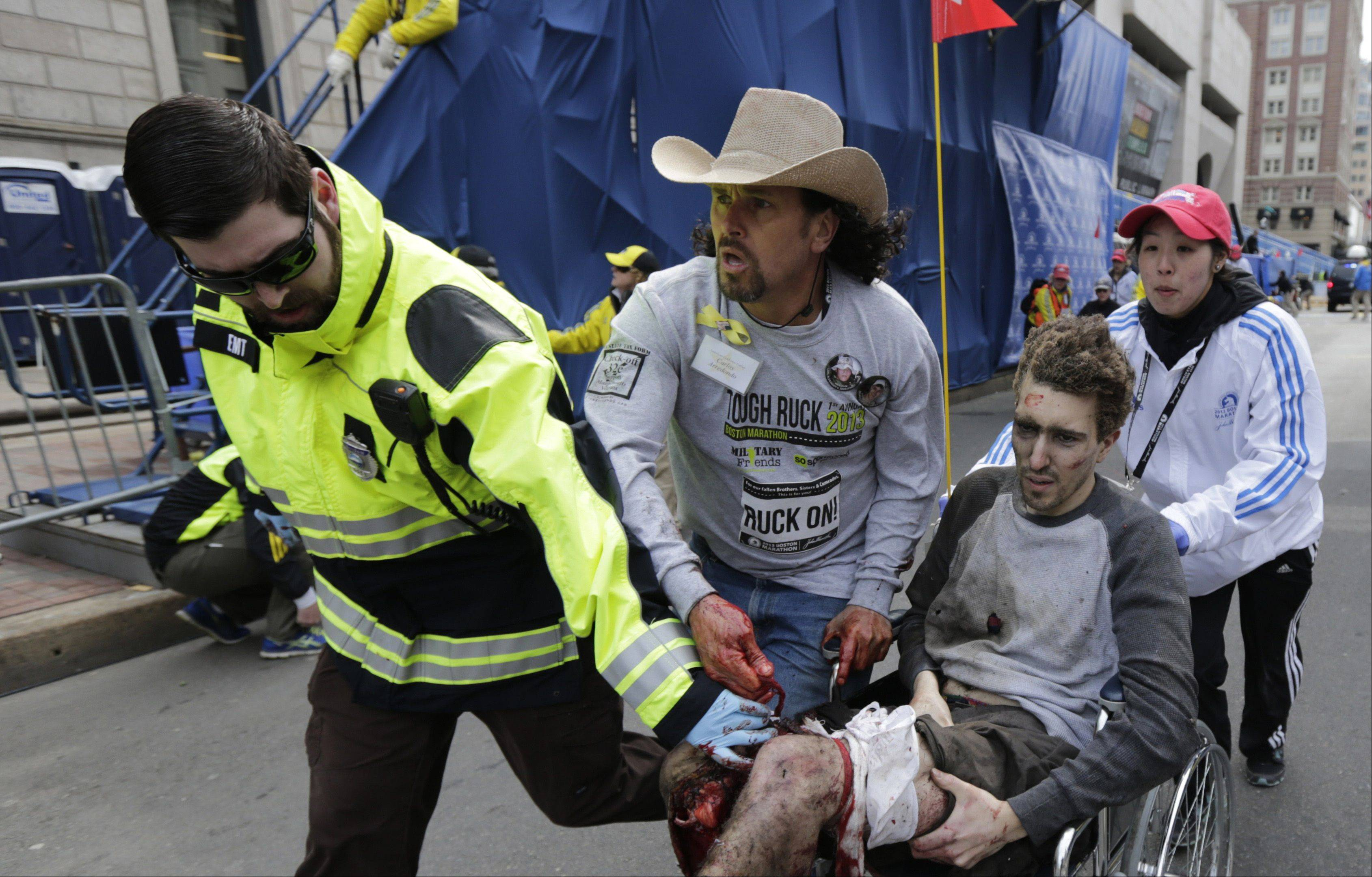 An emergency responder and volunteers, including Carlos Arredondo in the cowboy hat, push Jeff Bauman in a wheelchair after he was injured in an explosion near the finish line of the Boston Marathon Monday, April 15, 2013 in Boston.