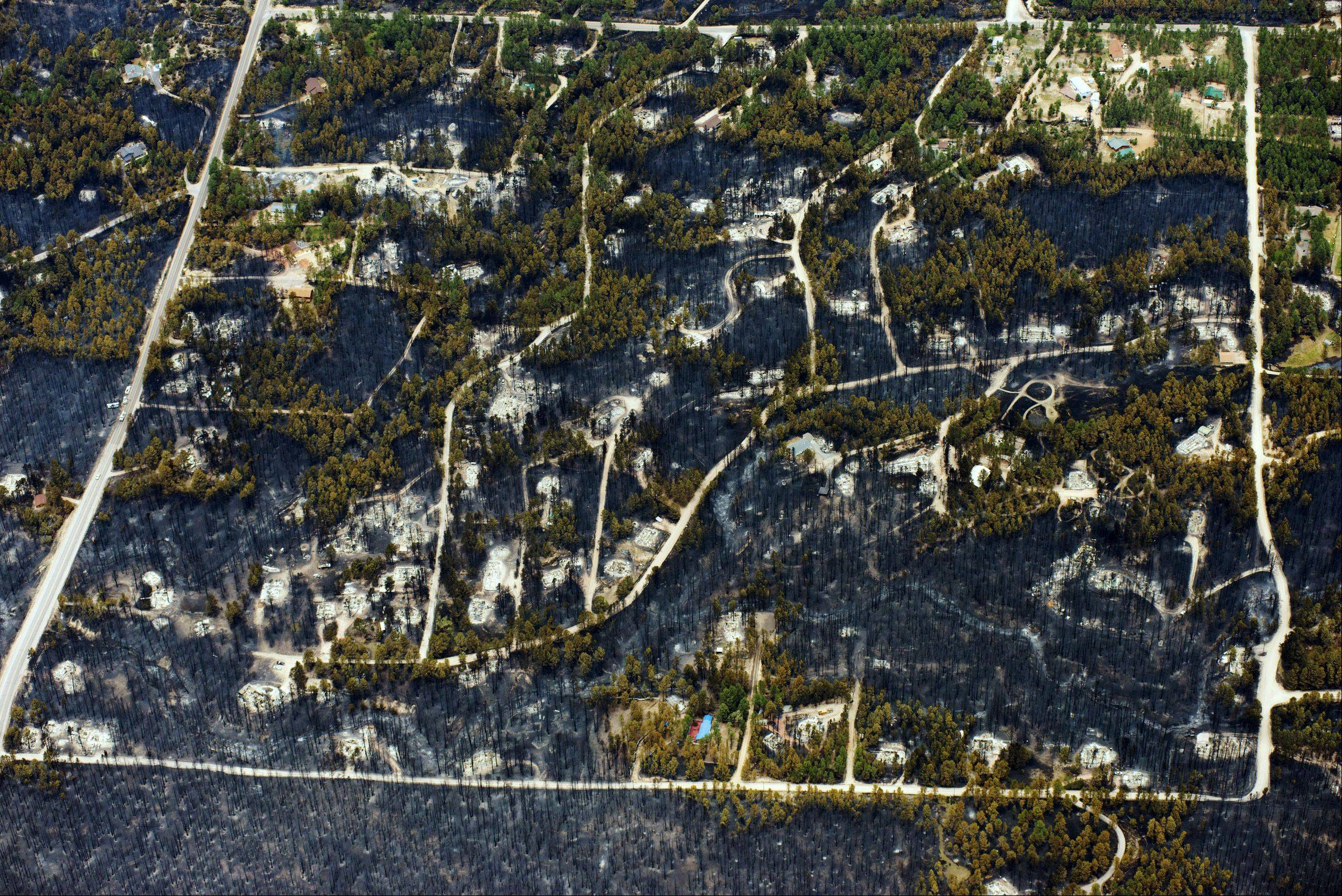 Burst trees and destroyed homes are left in the wake of a wildfire in the densely wooded Black Forest area northeast of Colorado Springs, Colo., Thursday, June 13, 2013. More than 350 homes were lost in what is now the most destructive wildfire in Colorado history.