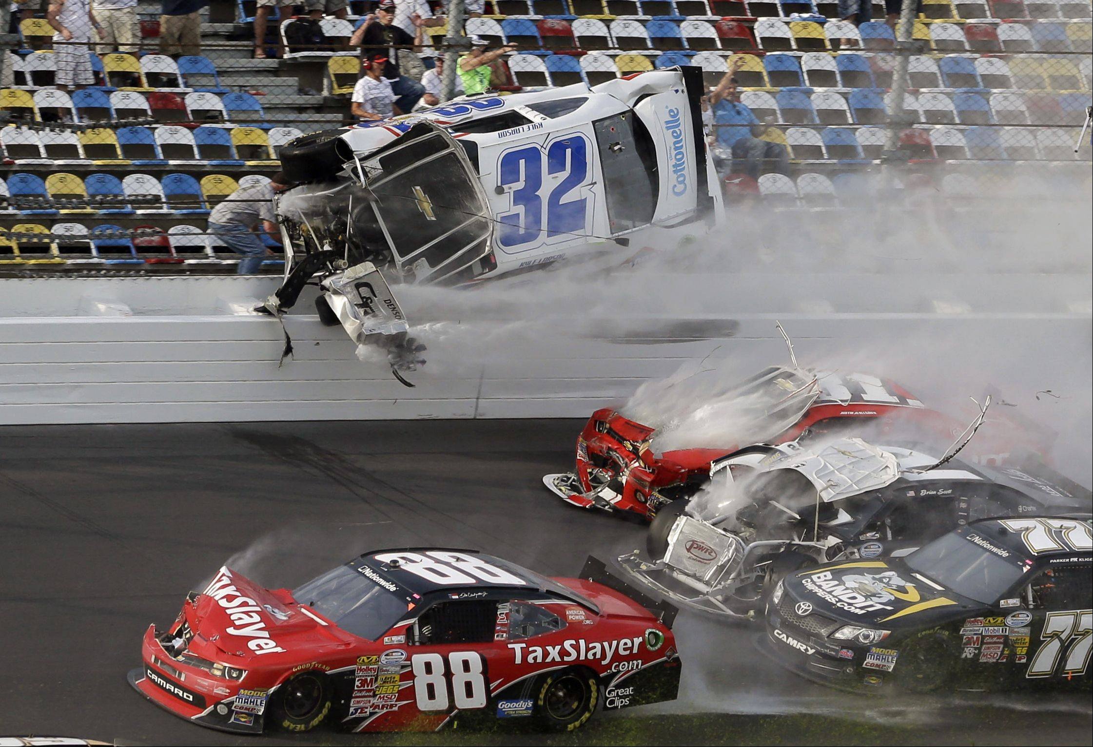 Kyle Larson (32) goes airborne and into the catch fence in a multicar crash involving Dale Earnhardt Jr. (88), Parker Kilgerman (77), Justin Allgaier (31) and Brian Scott (2) during the final lap of the NASCAR Nationwide Series auto race at Daytona International Speedway, Saturday, Feb. 23, 2013, in Daytona Beach, Fla.