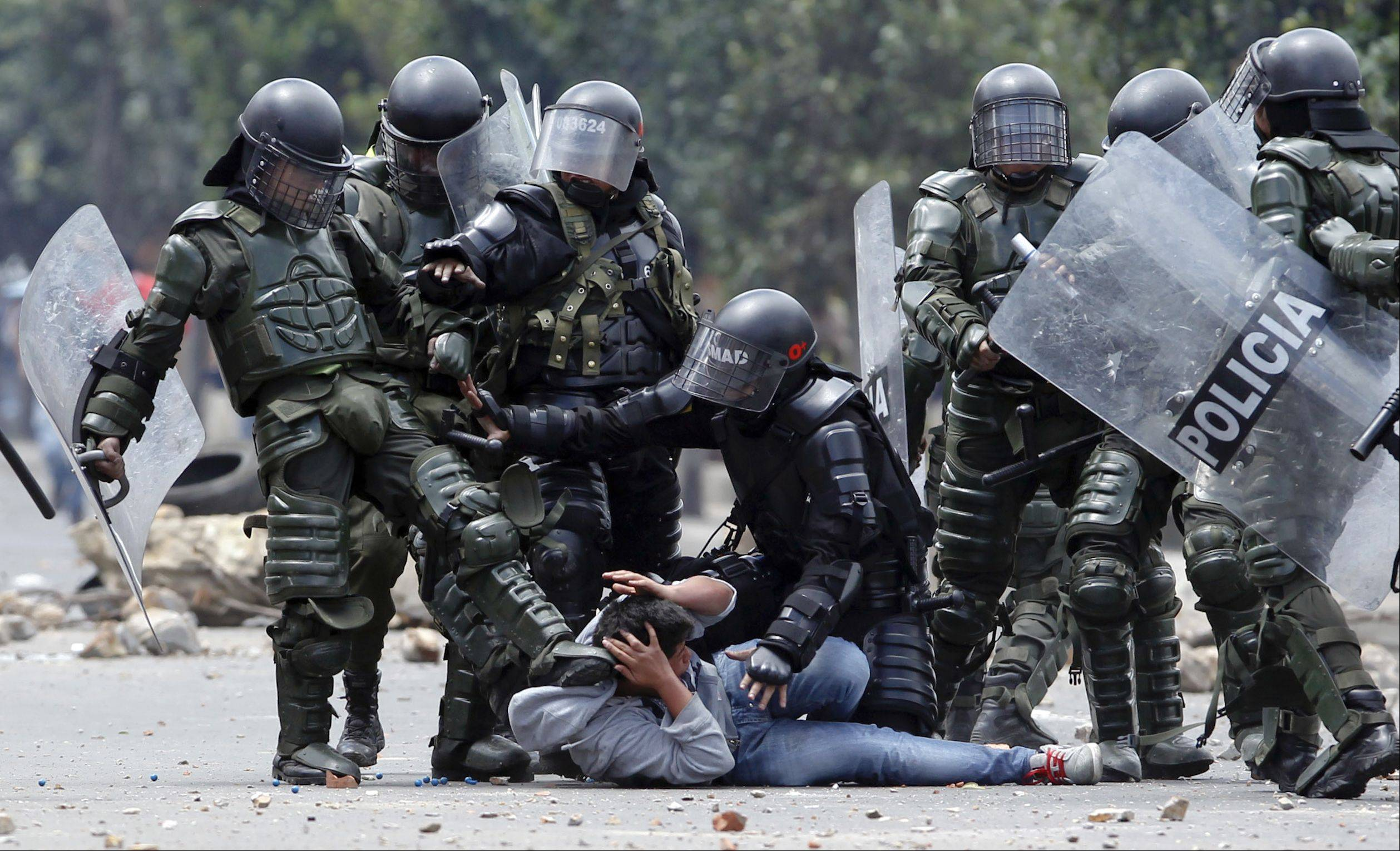 A riot police officer, left, kicks a protester as another, center, tries to protect him before his arrest during protests in Ubate, north of Bogota, Colombia, Monday, Aug. 26, 2013. Hundreds of protesters clashed with police in support of farmers who have been blockading Colombian highways for a week.