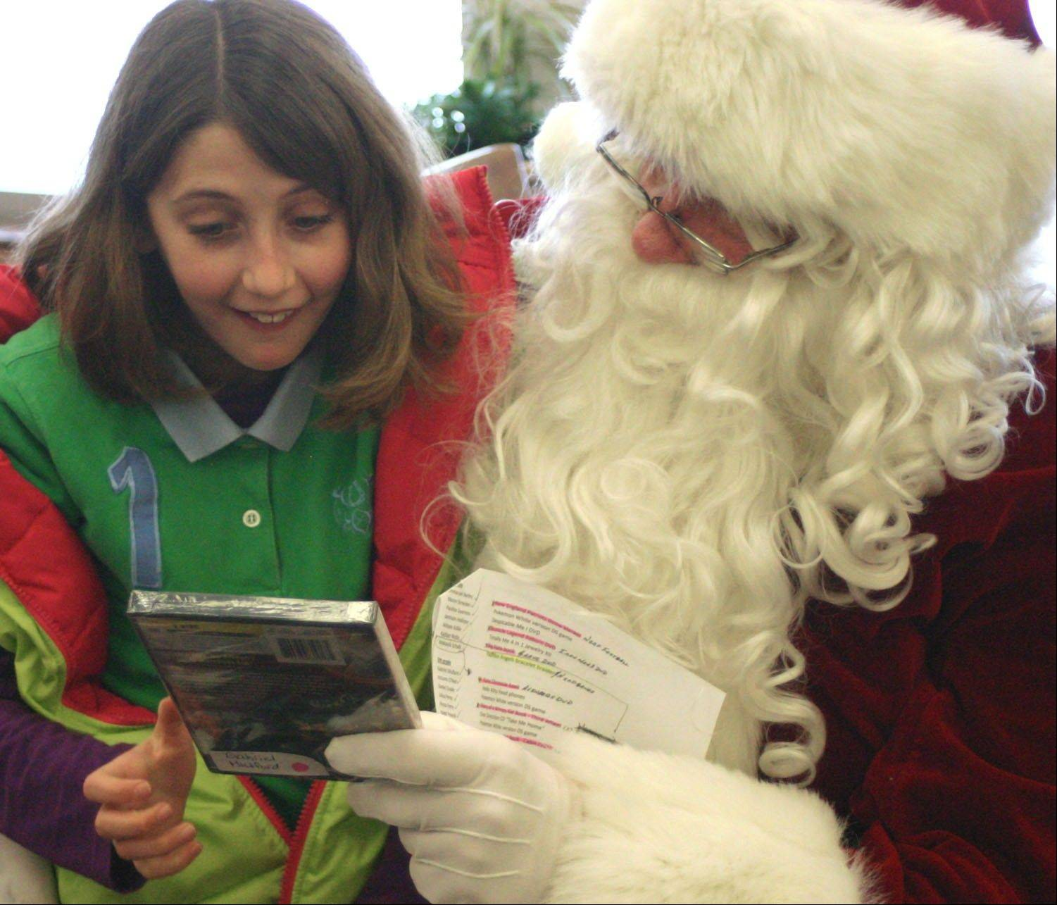 Mooseheart fifth-grader Gabriele Mulford's eyes light up when she receives a DVD from Santa Claus.